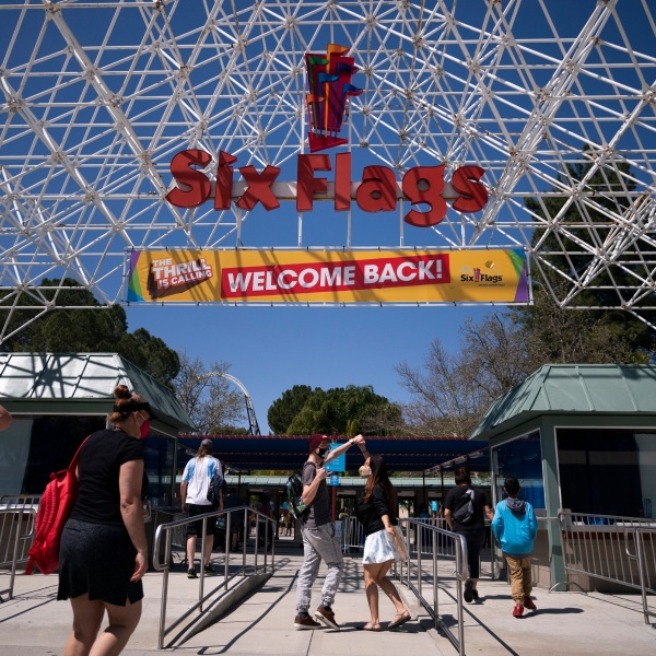 """A """"Welcome Back"""" sign at Six Flags Magic Mountain is seen on its first day of reopening to members and pass holders on April 1, 2021 in Valencia. (AP Photo/Jae C. Hong)"""