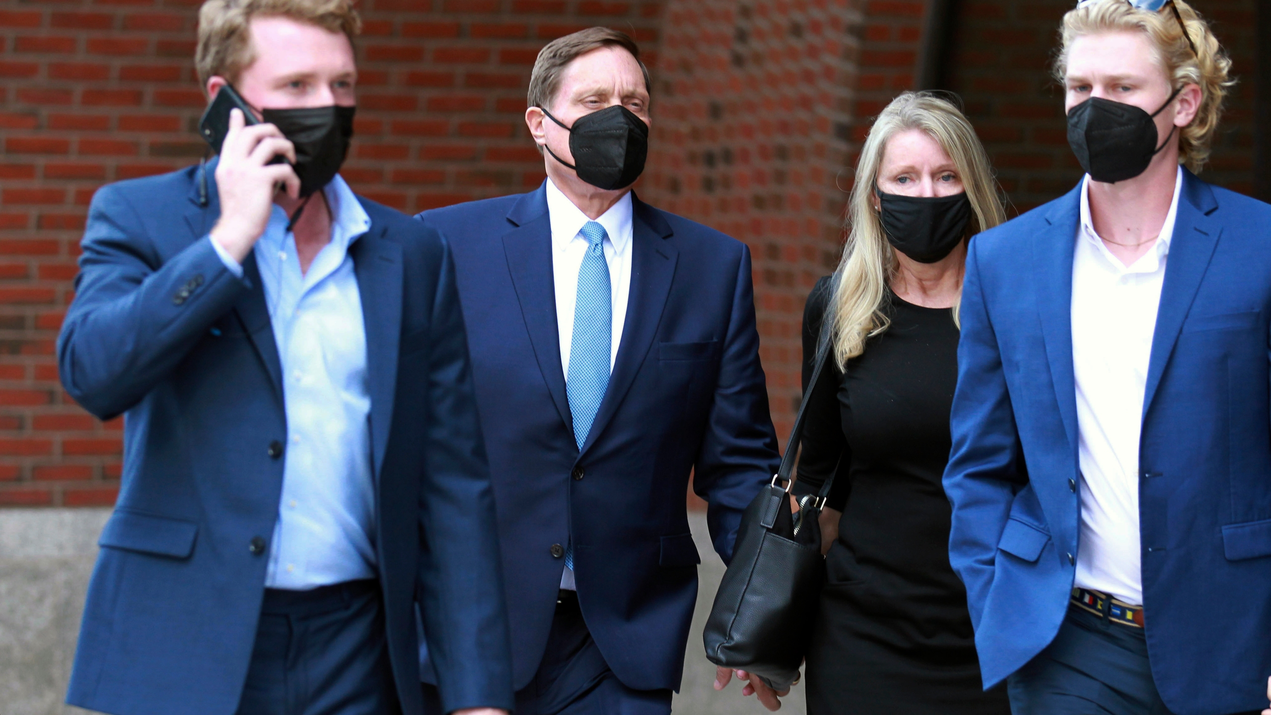 John Wilson, second left, holds his wife's hand, second right, as he leaves the John Joseph Moakley Federal Courthouse after the first day of his trial in the college admissions scandal on Sept.13, 2021, in Boston. (AP Photo/Stew Milne)