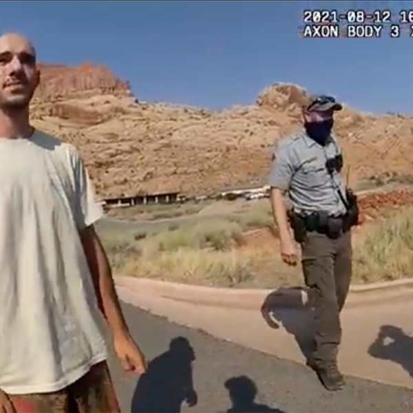 """This Aug. 12, 2021 file photo from video provided by The Moab Police Department shows Brian Laundrie talking to a police officer after police pulled over the van he was traveling in with his girlfriend, Gabrielle """"Gabby"""" Petito, near the entrance to Arches National Park. Laundrie, the boyfriend of Gabby Petito, whose body was found at a national park in Wyoming after a cross-country trip with him, has been charged with unauthorized use of a debit card as searchers continue looking for him in Florida swampland, federal authorities announced Thursday, Sept. 23, 2021. (The Moab Police Department via AP, File)"""