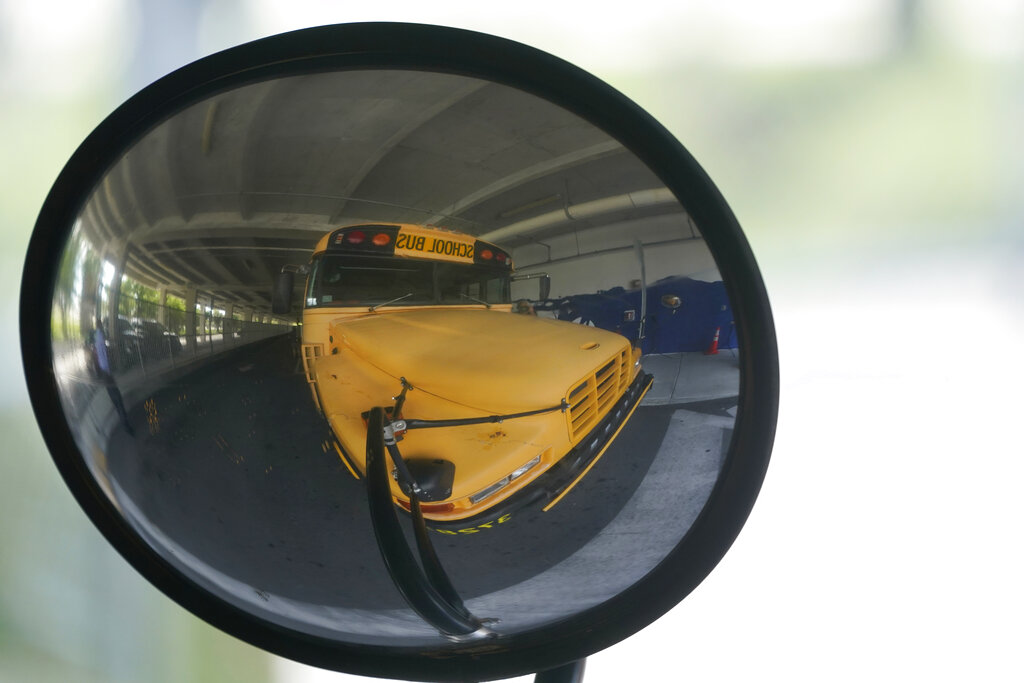 A diesel-powered school bus is reflected in a mirror at MAST Academy, Wednesday, Sept. 29, 2021, in Miami. (AP Photo/Wilfredo Lee)