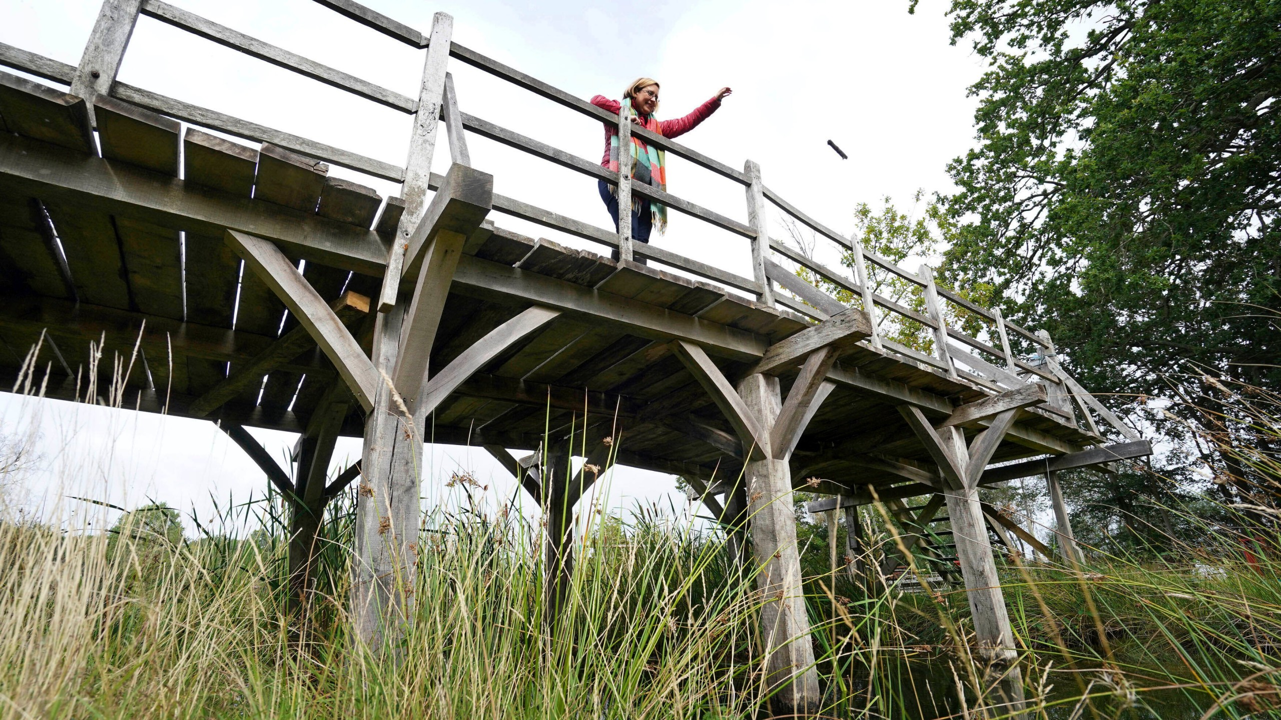 Silke Lohmann of Summers Place Auctions stands on the original Poohsticks Bridge from Ashdown Forest, featured in A.A. Milne's Winnie the Pooh books and E.H. Shepard's illustrations, near its original location in Tonbridge, Kent, England, Thursday, Sept. 30, 2021. (Gareth Fuller/PA via AP)