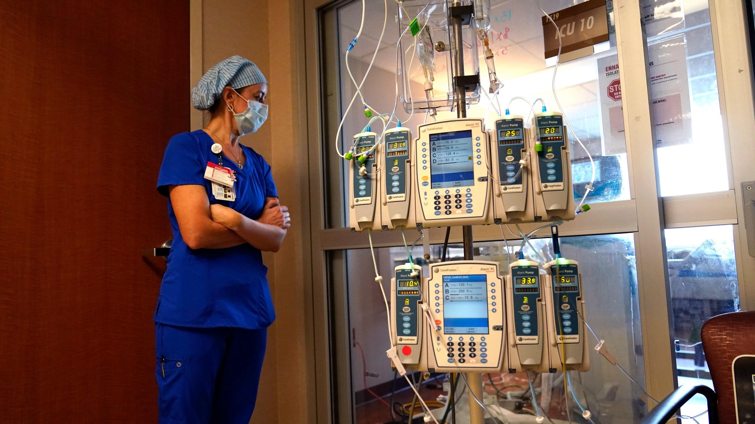 Nursing coordinator Beth Springer looks into a patient's room in a COVID-19 ward at the Willis-Knighton Medical Center in Shreveport, La., on Aug. 17, 2021. (Gerald Herbert / Associated Press)