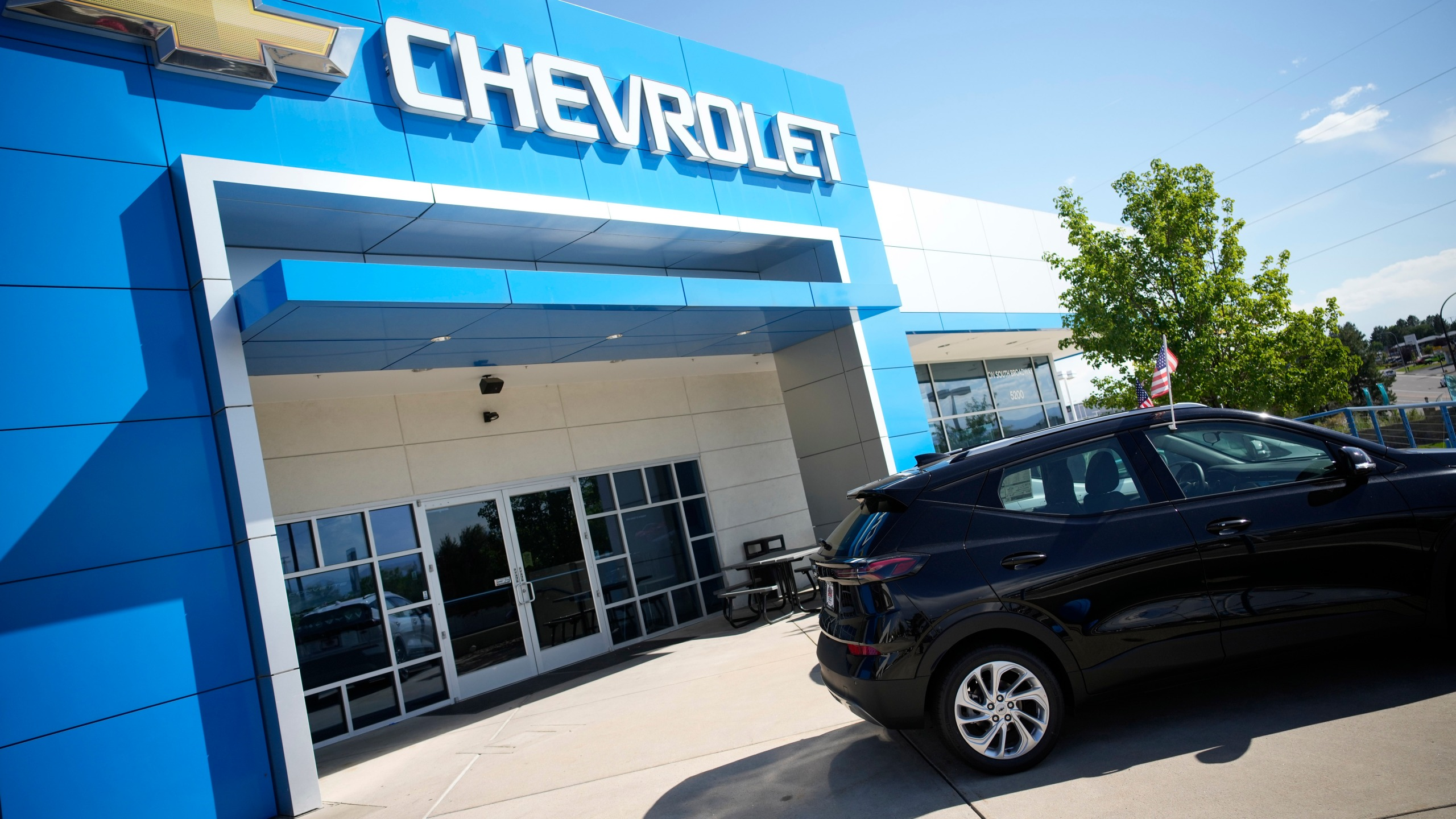 In this Sunday, Sept. 12, 2021, file photo, a pair of unsold 2022 Bolt electric vehicles sit outside a Chevrolet dealership in Englewood, Colo. (AP Photo/David Zalubowski, File)