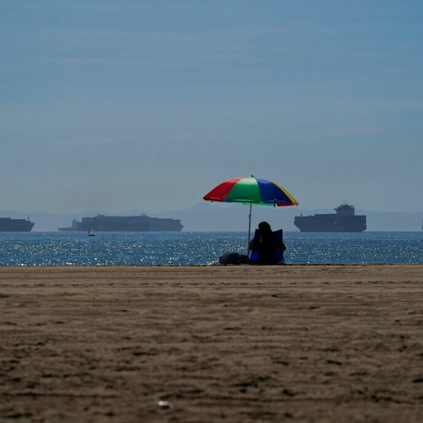 A beach goer sits on the beach in Seal Beach Calif., Friday, Oct. 1, 2021, as container ships waiting to dock at the Ports of Los Angeles and Long Beach are seen in the distance. (AP Photo/Jae C. Hong)
