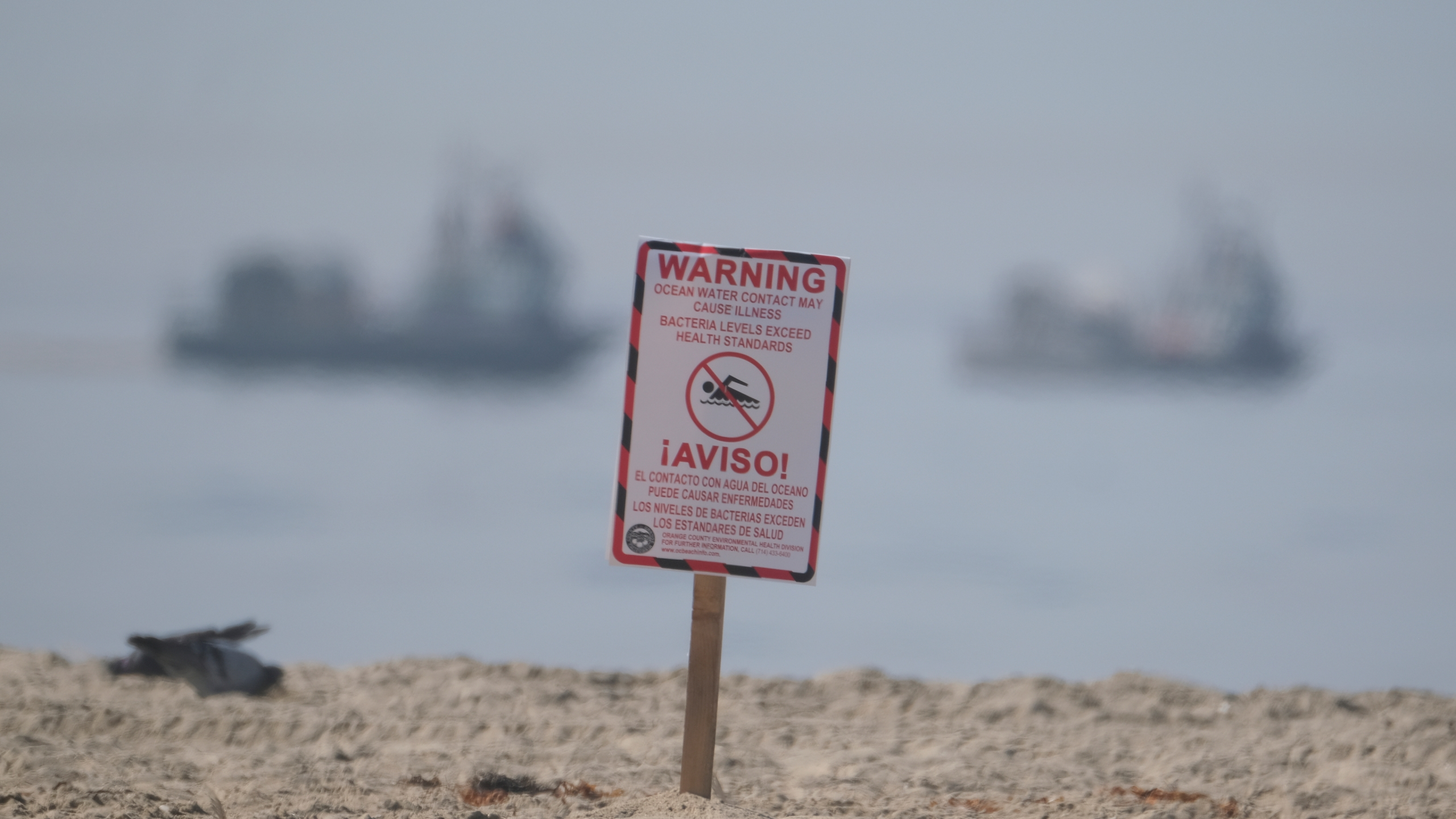 A posted sign warning about water contact may cause illness is posted by life guards after an oil spill in Huntington Beach, Calif., Sunday, Oct. 3, 2021. Vessels with the Marine Spill Response Corporation (MSRC) vessel, background, an oil spill removal organization (OSRO), deploy floating barriers around the largest oil spills in recent Southern California history fouled popular beaches and killed wildlife while crews scrambled Sunday to contain the crude before it spread further into protected wetlands. (AP Photo/Ringo H.W. Chiu)