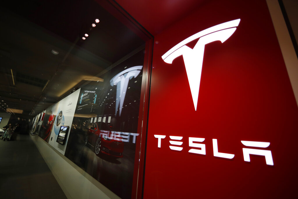In this Feb. 9, 2019, file photo, a sign bearing the company logo stands outside a Tesla store in Cherry Creek Mall in Denver. (AP Photo/David Zalubowski, file)