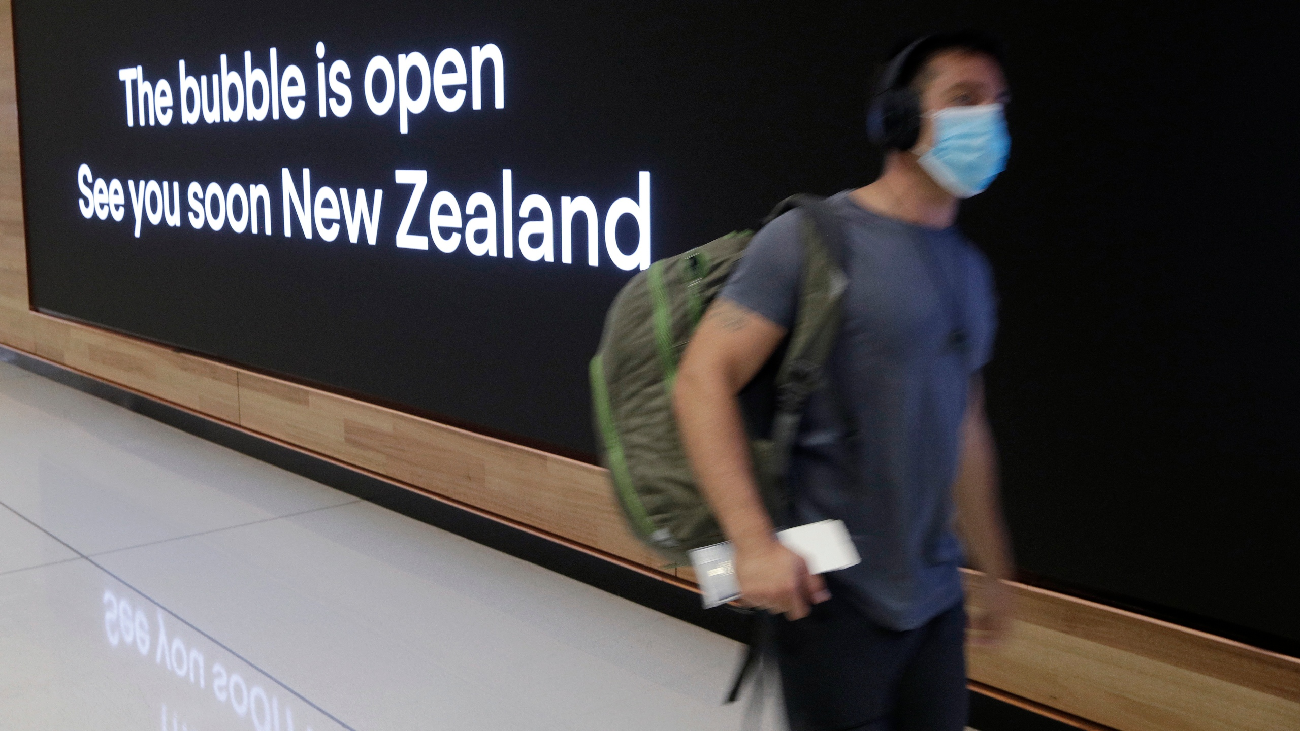 In this April 19, 2021, file photo a passenger travels through Sydney Airport, in Sydney, Australia. International tourists won't be welcomed back to Australia until next year, with the return of skilled migrants and students given higher priority, the prime minister said on Tuesday, Oct. 5, 2021. (AP Photo/Rick Rycroft, File)