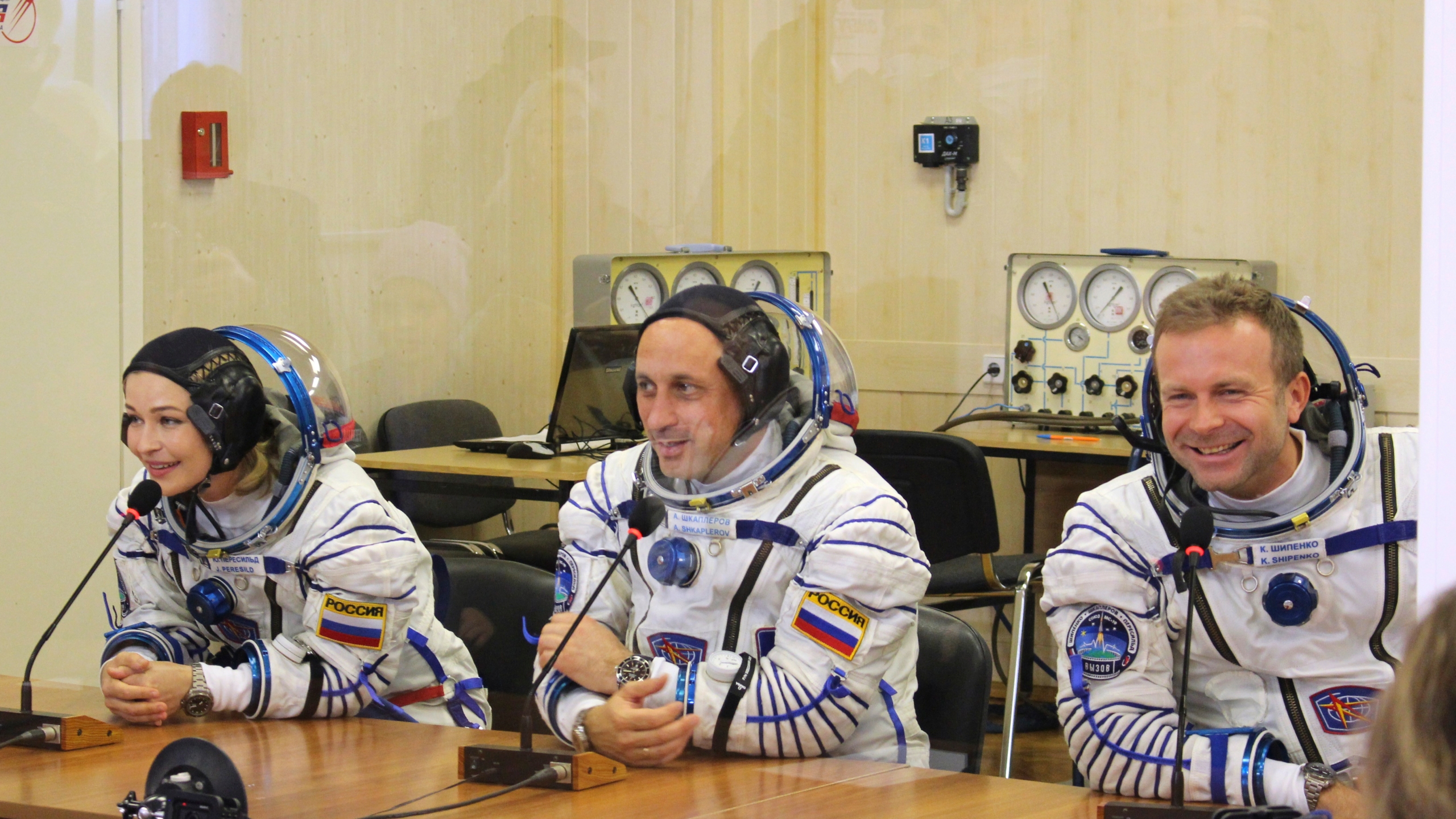 In this handout photo released by Roscosmos, actress Yulia Peresild, left, film director Klim Shipenko, right, and cosmonaut Anton Shkaplerov speak with their relatives through a safety glass prior the launch at the Baikonur Cosmodrome, Kazakhstan, Tuesday, Oct. 5, 2021. Actress Yulia Peresild and film director Klim Shipenko blasted off Tuesday for the International Space Station in a Russian Soyuz spacecraft together with cosmonaut Anton Shkaplerov, a veteran of three space missions, to make a feature film in orbit. (Roscosmos Space Agency via AP)