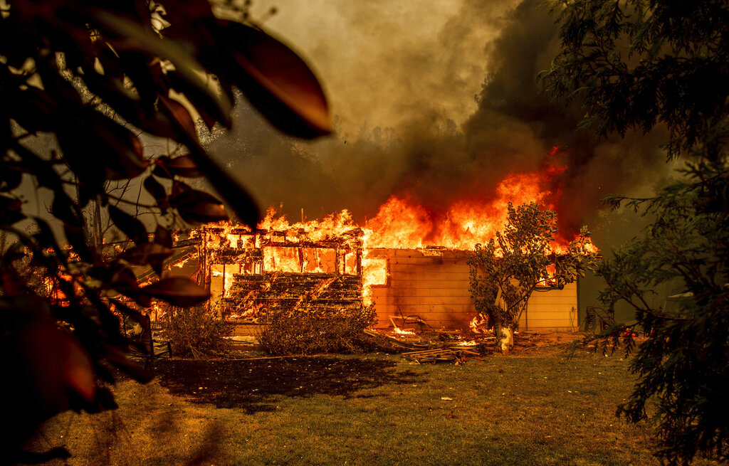 In this Sept. 23, 2021, file photo, flames consume a house near Old Oregon Trail as the Fawn Fire burns north of Redding in Shasta County, Calif. (AP Photo/Ethan Swope, File)