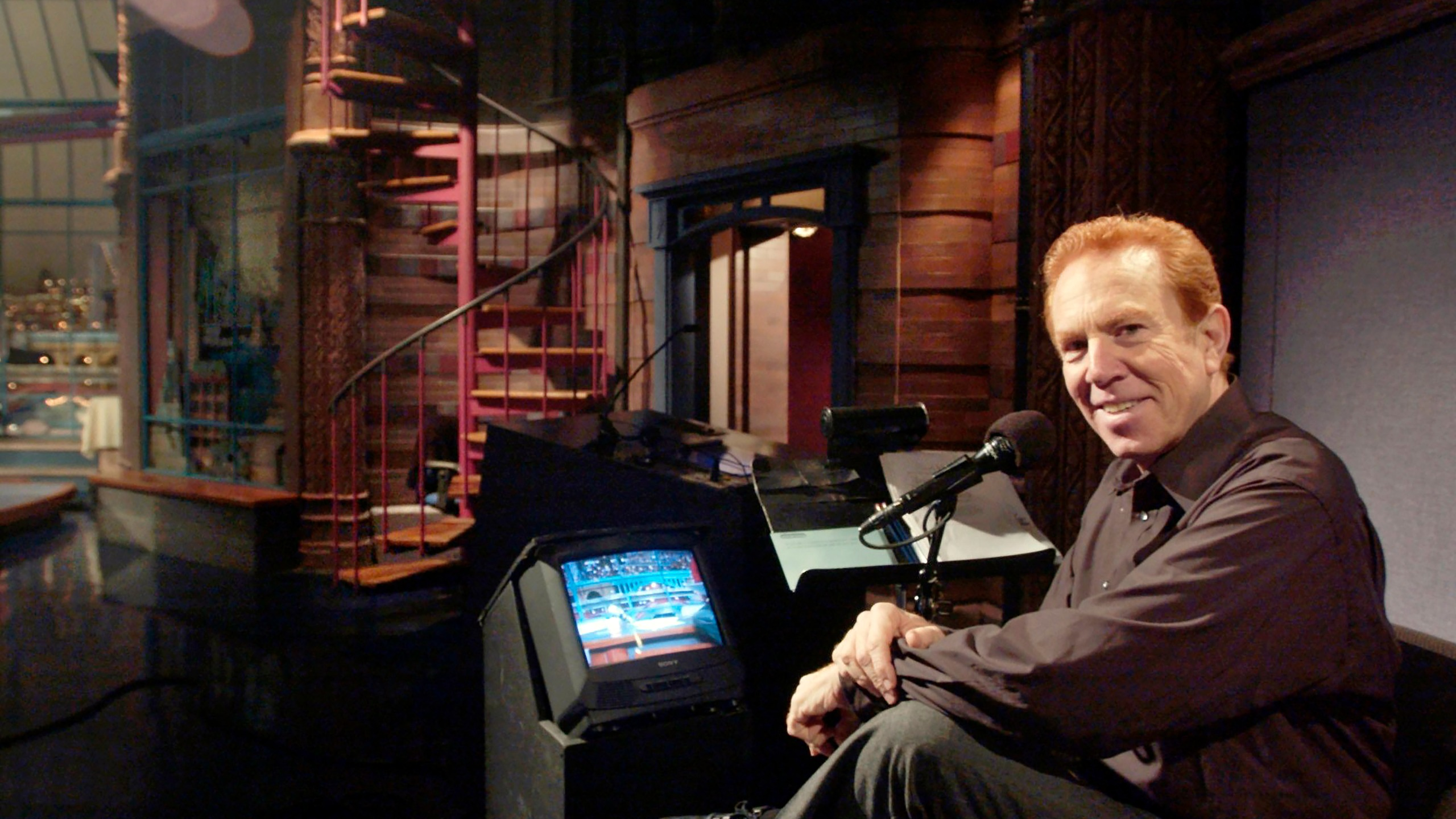 """In this Nov. 20, 2003, file photo, """"Late Show With David Letterman'' announcer Alan Kalter poses in the the Late Show studio in New York. Kalter, the quirky, red-headed announcer for David Letterman for two decades who frequently appeared in the show's comedy bits, has died Monday, Oct. 4, 2021, at Stamford Hospital in Connecticut. He was 78. (Andrew Sullivan/Hearst Connecticut Media via AP, File)"""