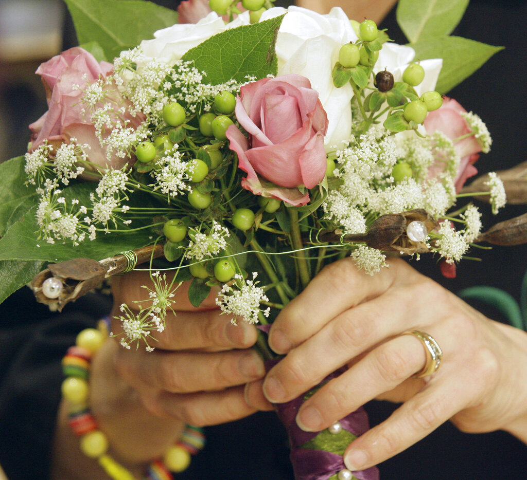 In this Thursday, Nov. 30, 2006, file photo, Leanne Kesler, the president of the Floral Design Institute is shown working with a bridal bouquet in Portland, Ore. (AP Photo/Rick Bowmer, File)