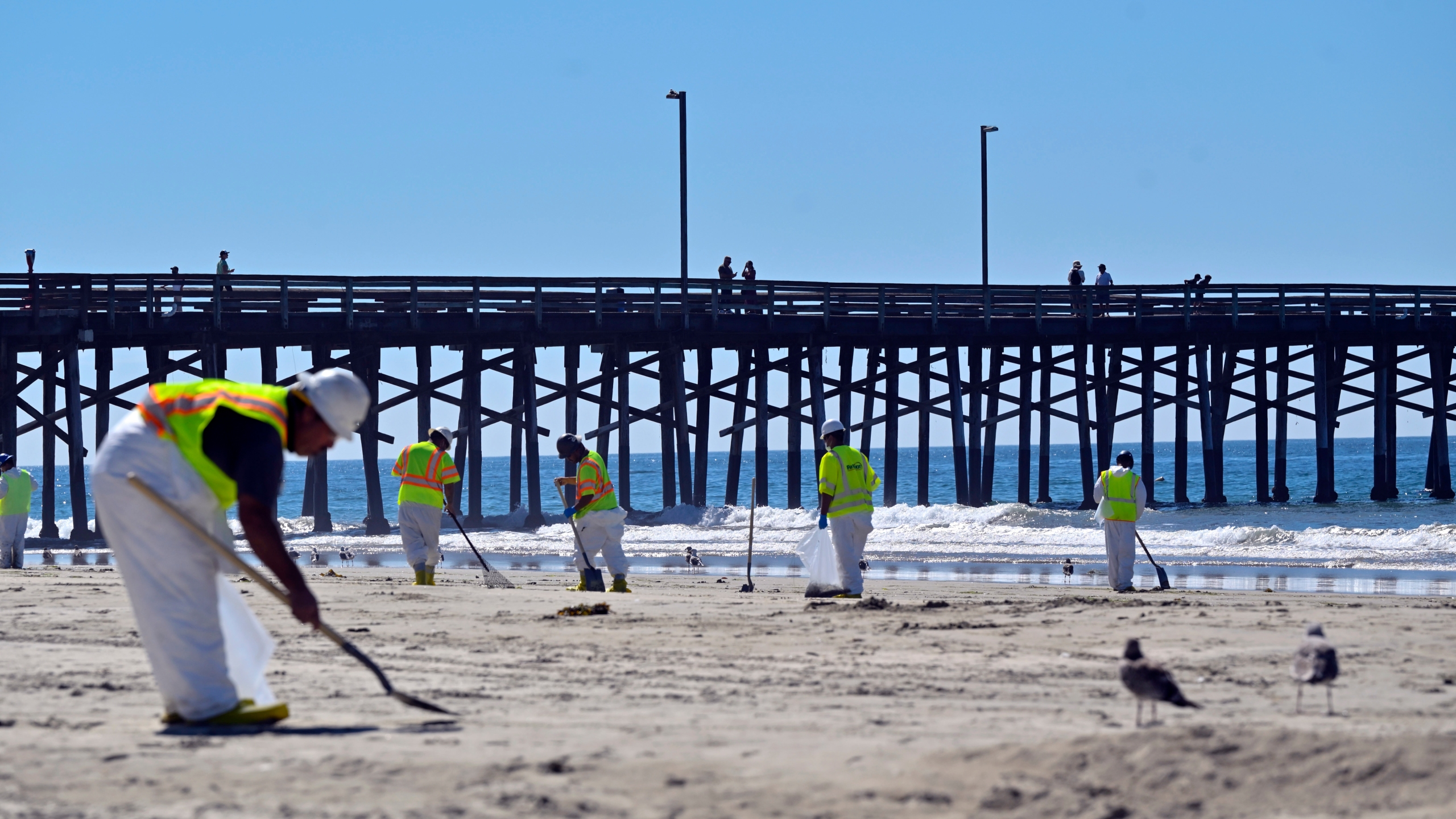 Workers clean oil from the sand, south of the pier in Newport Beach on Oct. 5, 2021. (Jeff Gritchen / The Orange County Register via Associated Press)