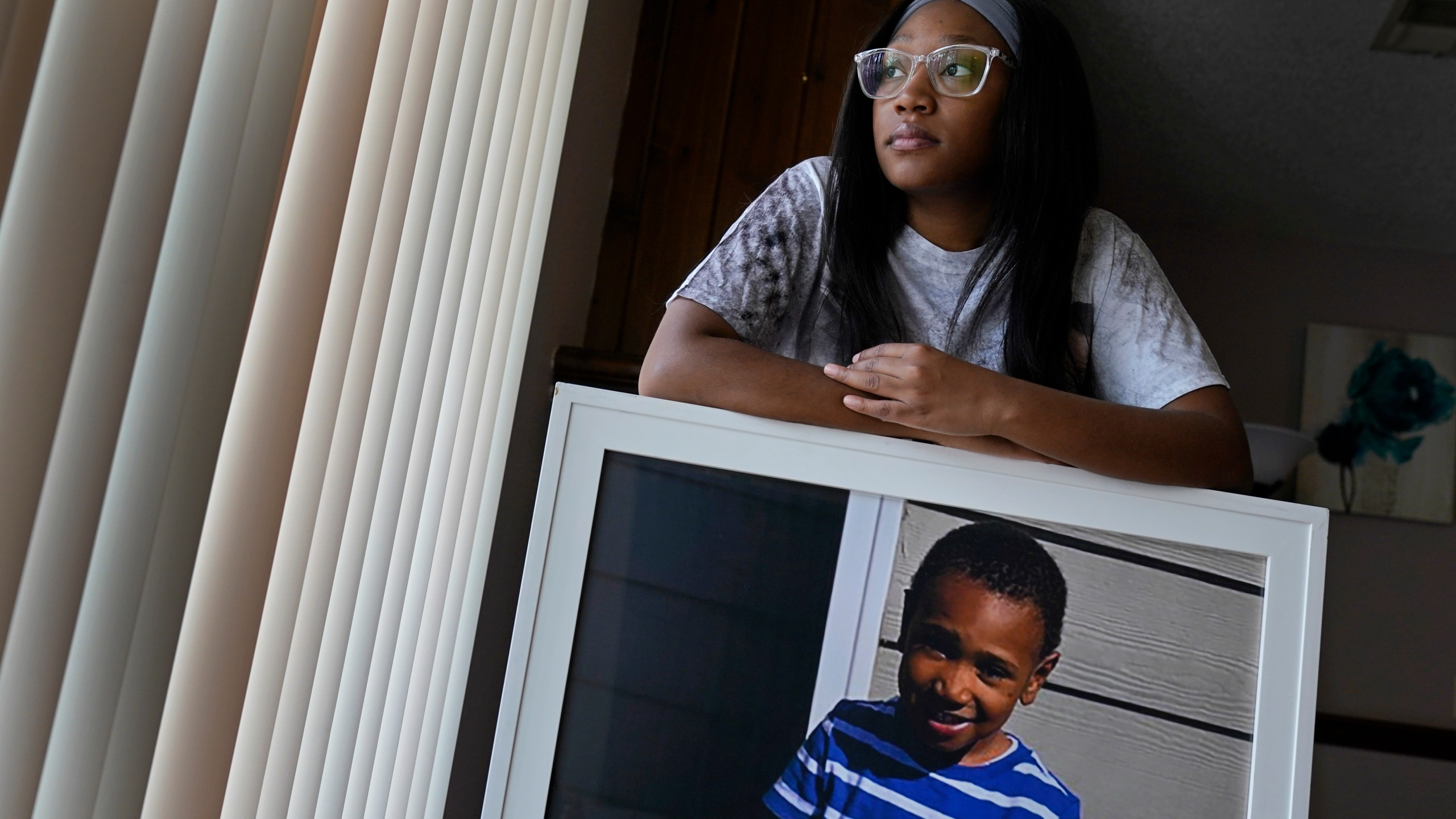 Charron Powell stands with a photo of her son, LeGend Talieferro, at her home in Raytown, Mo. on Sunday, Oct. 3, 2021. LeGend was 4 years old when he was fatally shot June 29, 2020 while he was sleeping in an apartment staying with his father. (AP Photo/Charlie Riedel)