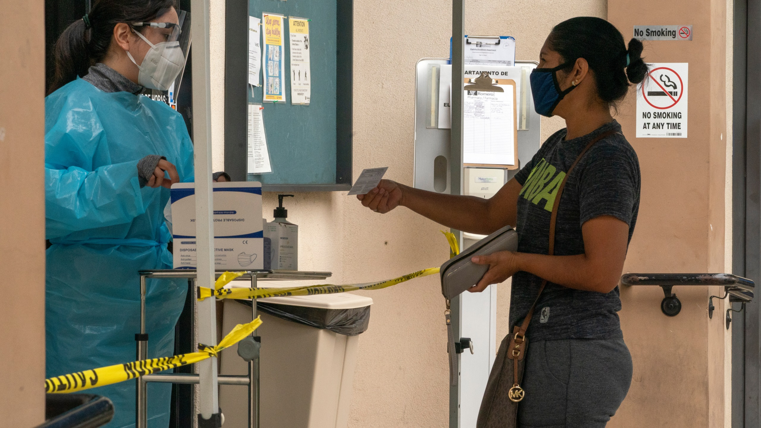 In this July 26, 2021, file photo, a patient shows her COVID-19 vaccine card at the Clínica Monseñor Oscar A. Romero in the Pico-Union district of Los Angeles. (Damian Dovarganes/Associated Press)