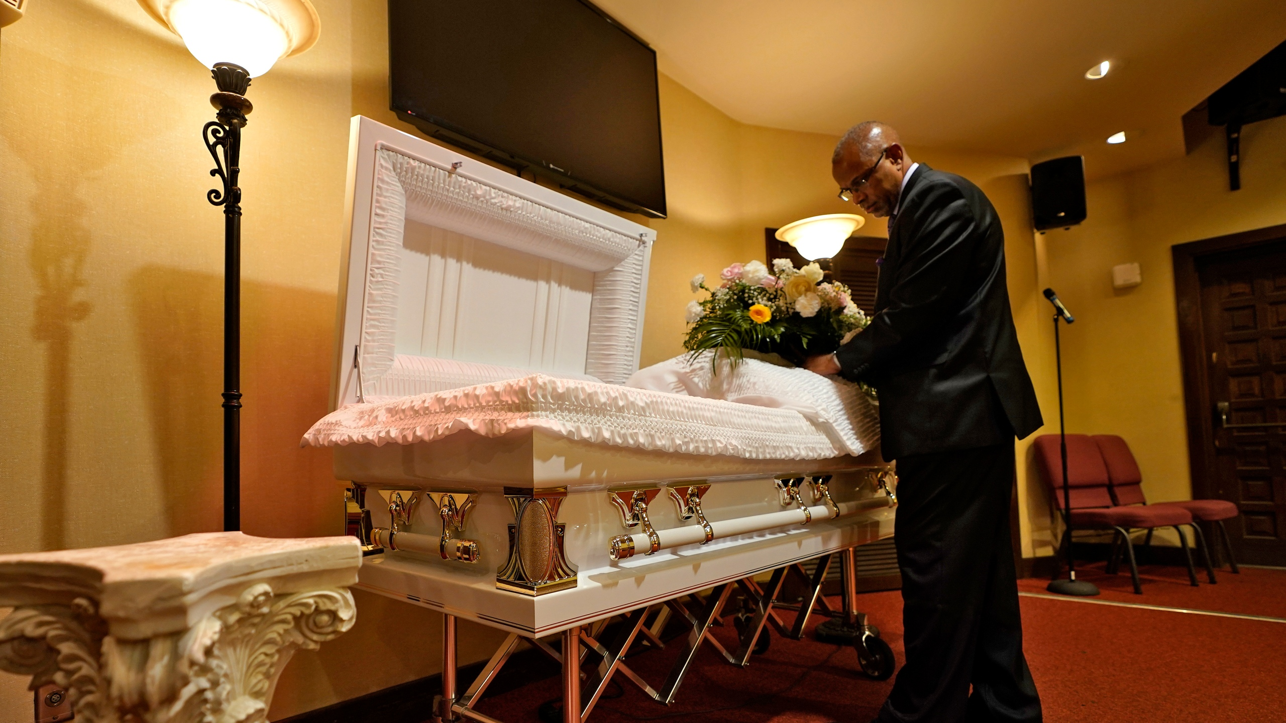 In this Thursday, Sept. 2, 2021 file photo, a funeral director arranges flowers on a casket before a service in Tampa, Fla. According to a study published Thursday, Oct. 7, 2021, by the medical journal Pediatrics, the number of U.S. children orphaned during the COVID-19 pandemic may be larger than previously estimated, and the toll has been far greater among Black and Hispanic Americans. (AP Photo/Chris O'Meara, File)