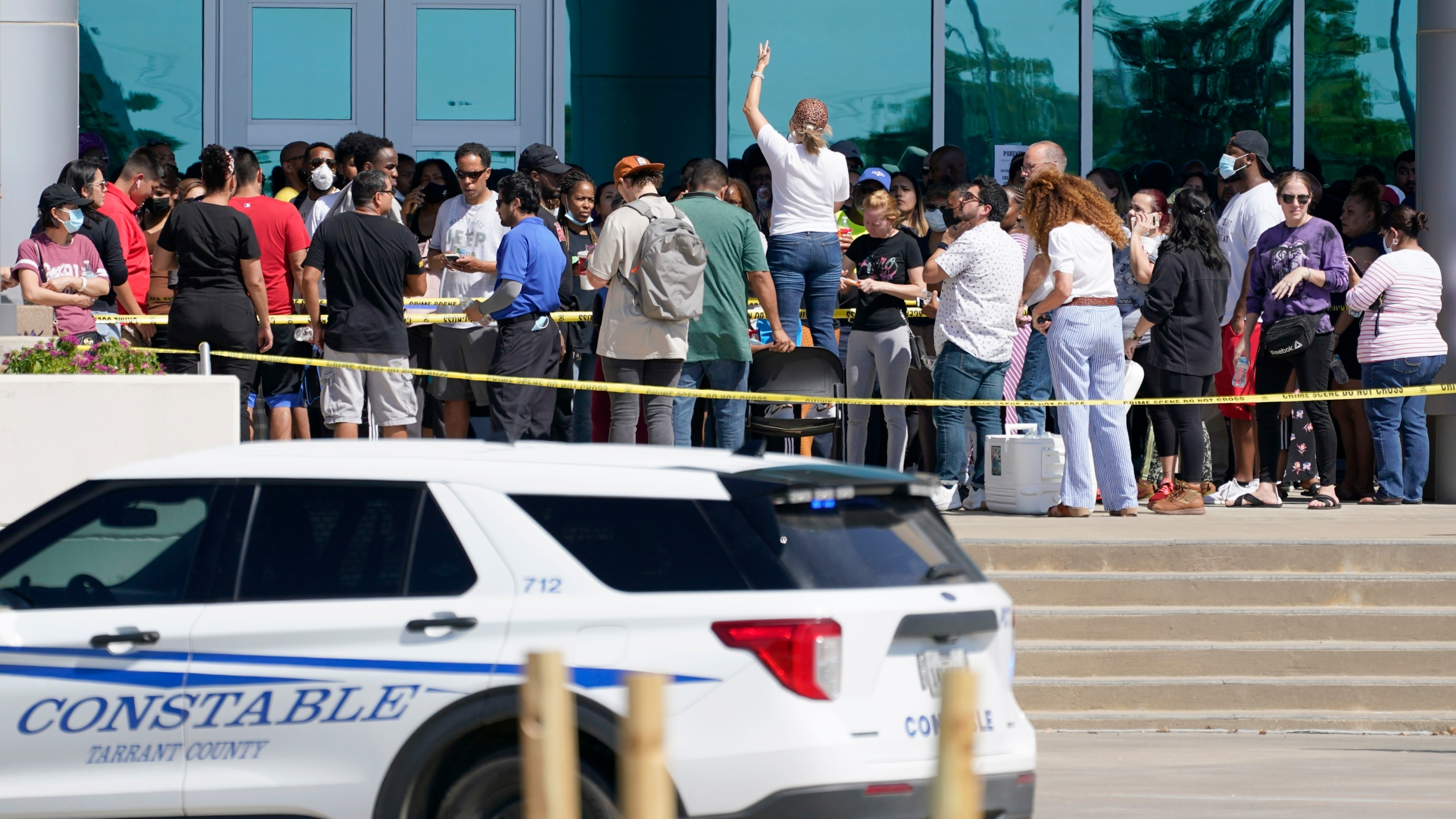 Families are addressed by an unidentified person at center, as they wait to be reunited with their children at the Mansfield ISD Center For The Performing Arts, Wednesday, Oct. 6, 2021, in Mansfield, Texas, following a school shooting at Timberview High School in Arlington. (AP Photo/Tony Gutierrez)