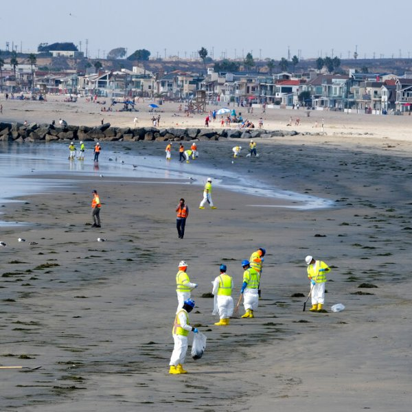 Workers in protective suits clean the contaminated beach after an oil spill, Wednesday, Oct. 6, 2021 in Newport Beach, Calif. (AP Photo/Ringo H.W. Chiu)