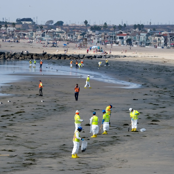 Workers in protective suits clean the contaminated Newport Beach on Oct. 6, 2021, after an oil spill off the coast. (Ringo H.W. Chiu / Associated Press)