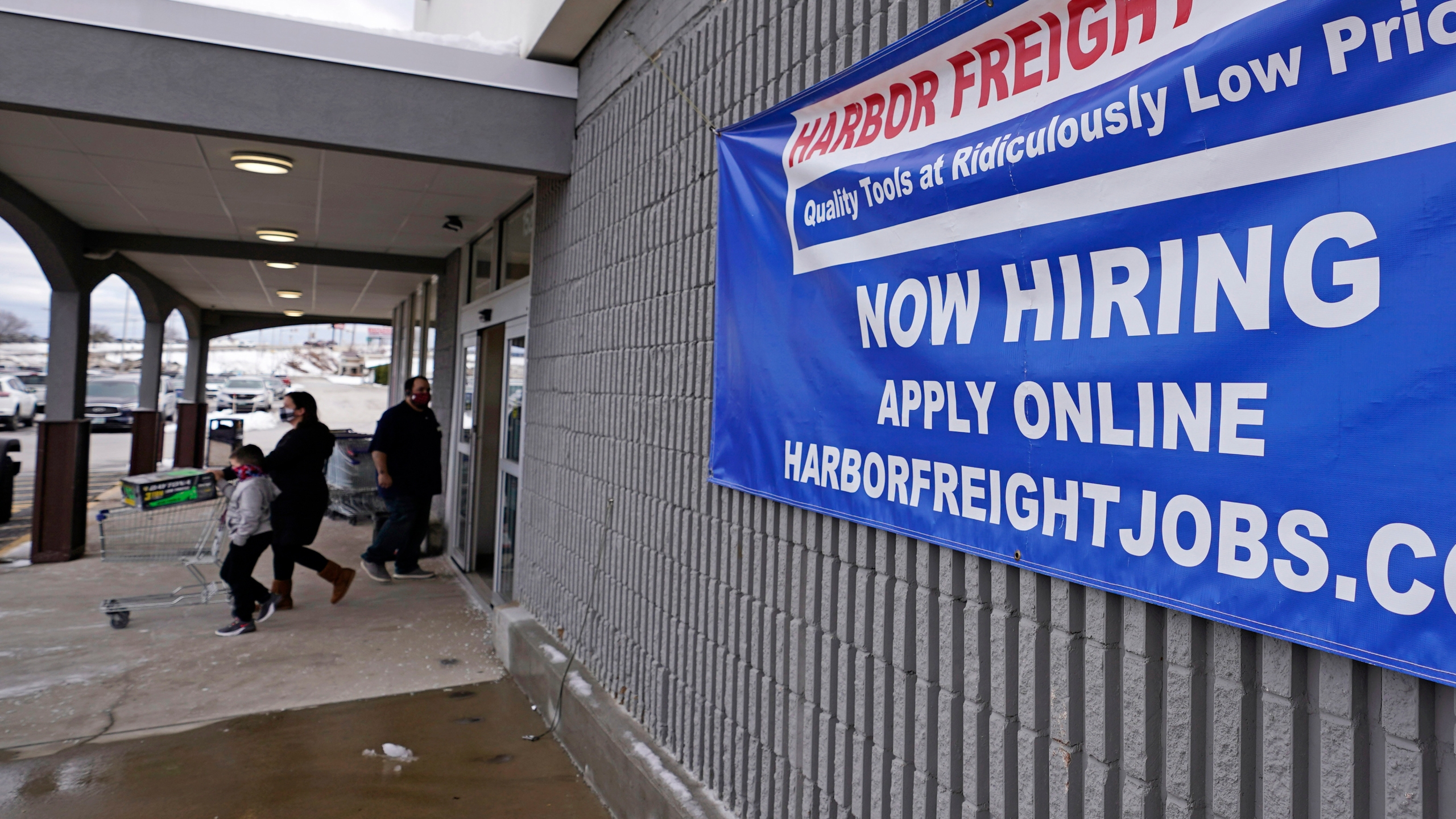 """In this Dec. 10, 2020, file photo, a """"Now Hiring"""" sign hangs on the front wall of a Harbor Freight Tools store in Manchester, N.H. When the U.S. government issues the September jobs report on Friday, Oct. 8, 2021, the spotlight will fall not only on how many people were hired last month. A second question will command attention, too: Are more people finally starting to look for work? (AP Photo/Charles Krupa, File)"""