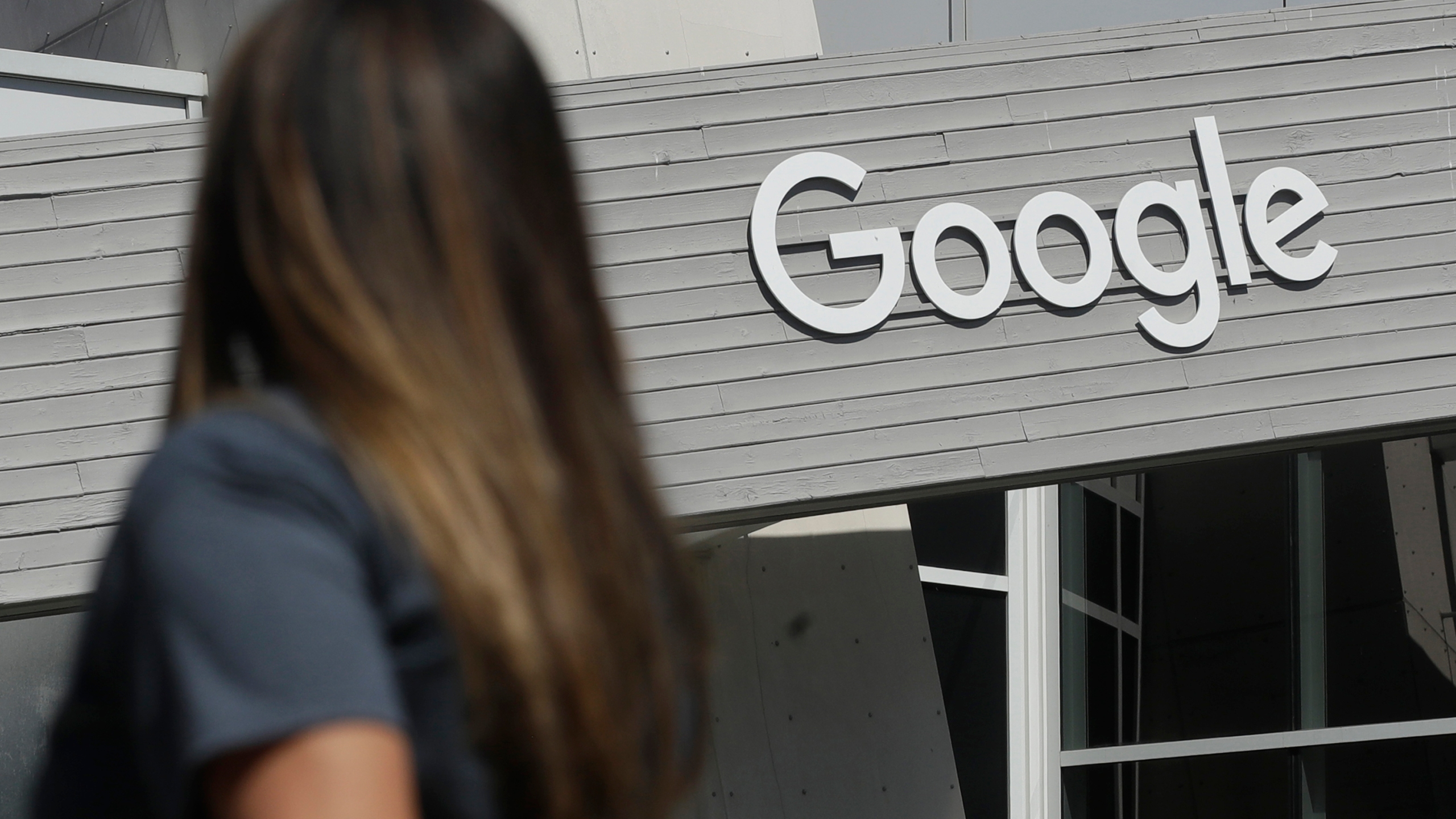In this Sept. 24, 2019, file photo, a woman walks below a Google sign on the campus in Mountain View, Calif. Google on Thursday, Oct. 7, 2021, will no longer allow digital ads promoting false climate change claims to appear next to the content of other publishers, hoping to deny money to those making such claims and to stop the spread of misinformation on its platform. (AP Photo/Jeff Chiu, File)