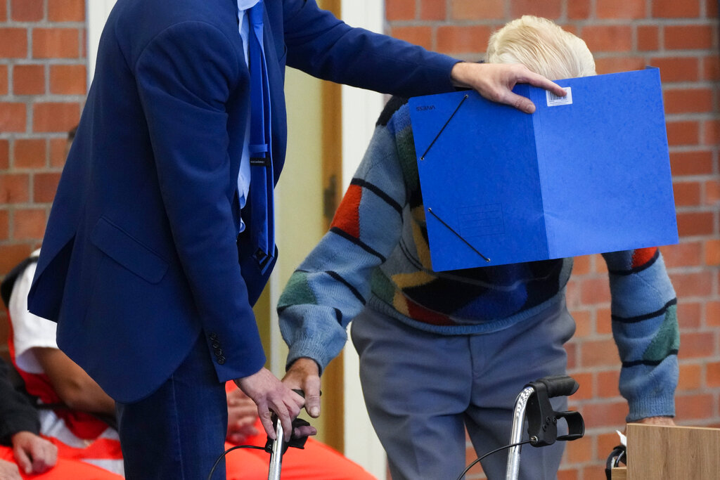 In this Thursday, Oct. 7, 2021 file photo, lawyer Stefan Waterkamp covers the face of accused Josef S. as they arrive at a courtroom in Brandenburg, Germany. (AP Photo/Markus Schreiber, File)