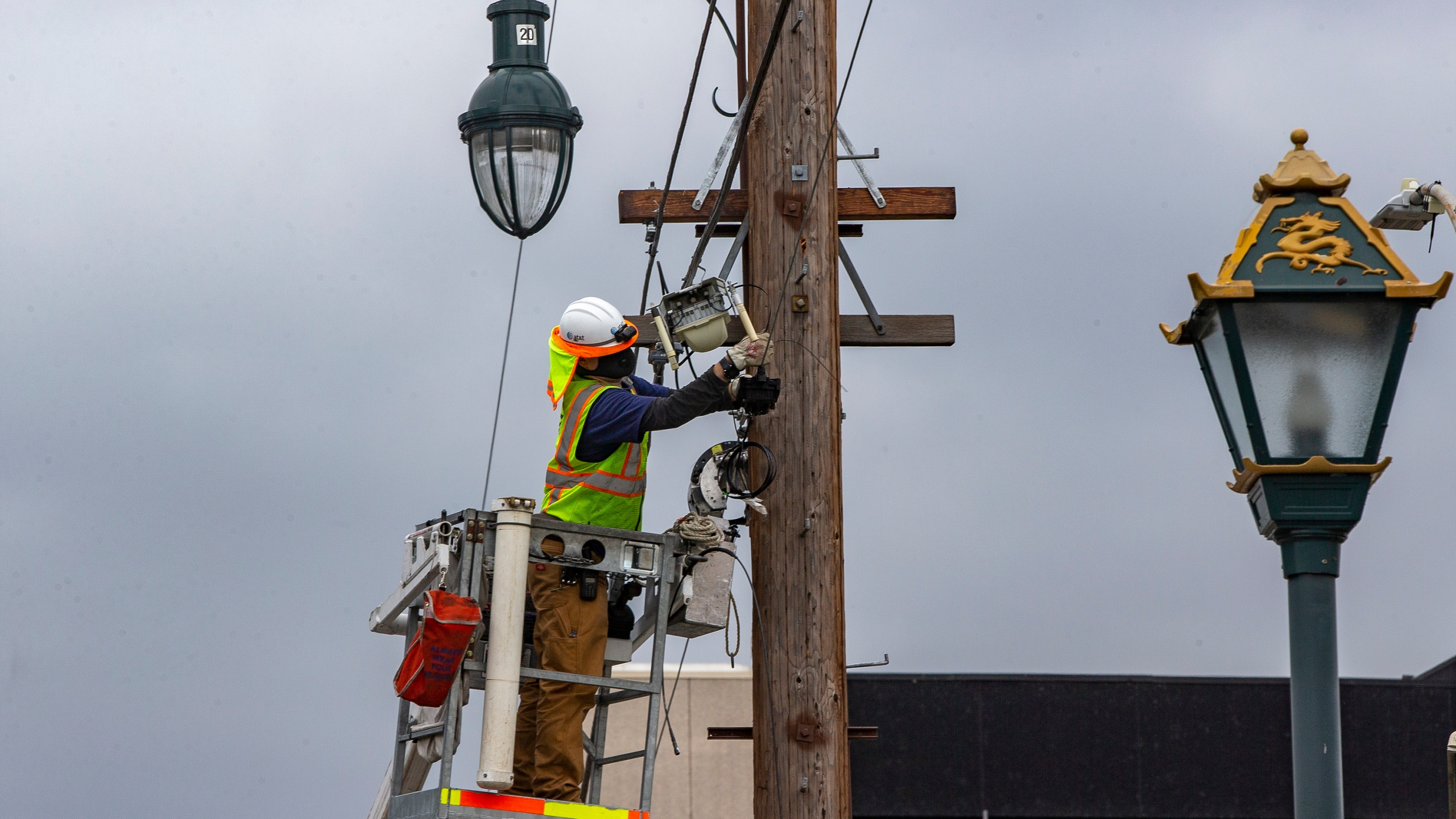 AT&T workers deploy fiber optic lines for a cellphone tower station in the Chinatown neighborhood of Los Angeles on June 5, 2020. (Damian Dovarganes / Associated Press)
