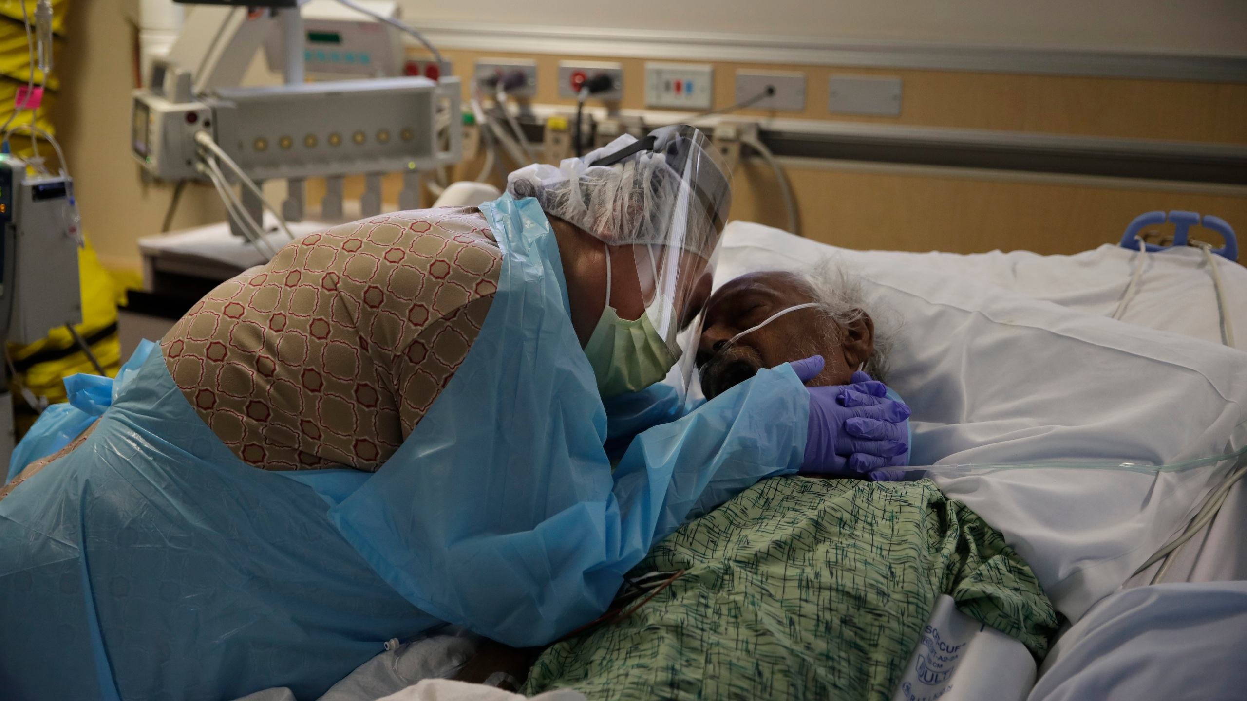 In this Friday, July 31, 2020, file photo, Romelia Navarro, 64, weeps while hugging her husband, Antonio, in his final moments in a COVID-19 unit at St. Jude Medical Center in Fullerton, Calif. On Monday, Oct. 11, 2021, California's coronavirus death toll reached 70,000. (AP Photo/Jae C. Hong, File)