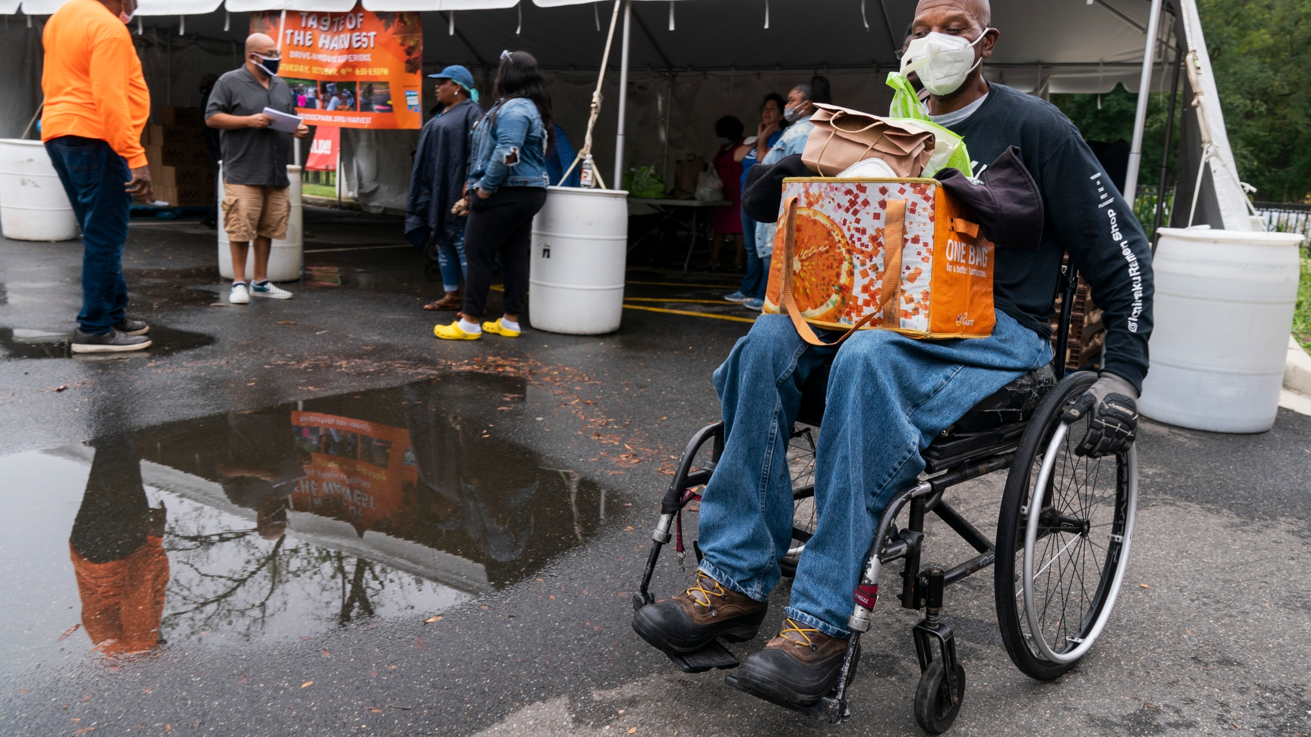 Randy Horton, of Washington, holds bags of food in his lap as he leaves in his wheelchair after receiving a bag of produce and a lunch meal at the Town Hall Education Arts & Recreation Campus (THEARC), Wednesday, Oct. 6, 2021, in Washington. (AP Photo/Jacquelyn Martin)