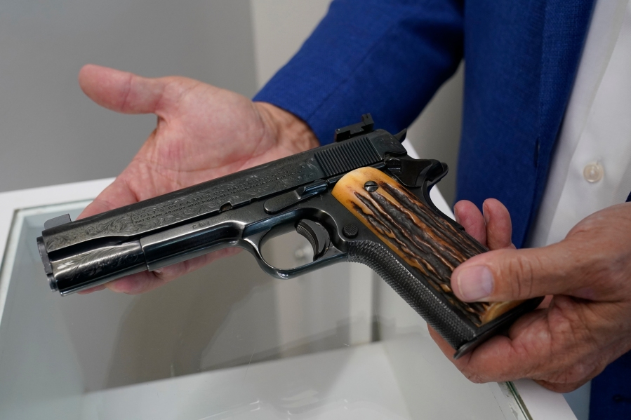 Brian Witherell displays a Colt .45-caliber pistol that once belonged to mob boss Al Capone, at Witherell's Auction House in Sacramento on Aug. 25, 2021. (Rich Pedroncelli / Associated Press)
