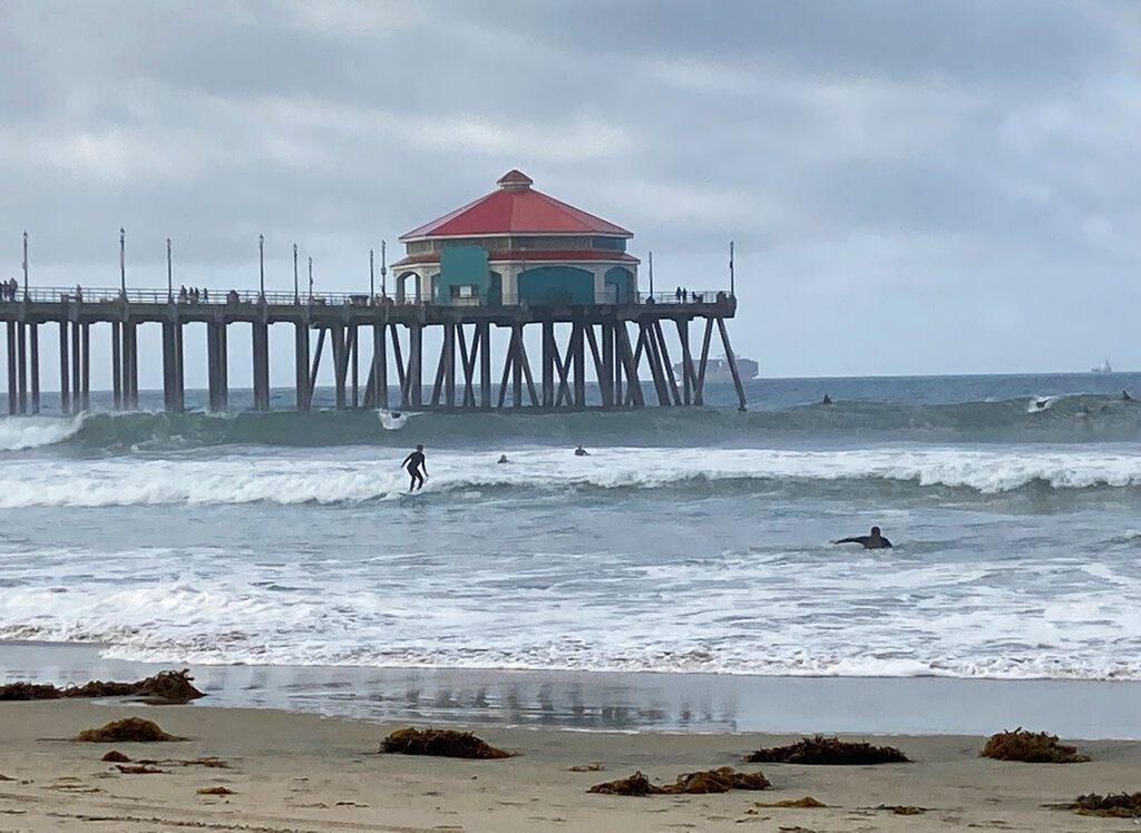 Surfers and swimmers return to the Huntington Beach pier waves since the crude oil spill at the California beach, Monday, Oct. 11, 2021. (AP Photo/Amy Taxin)