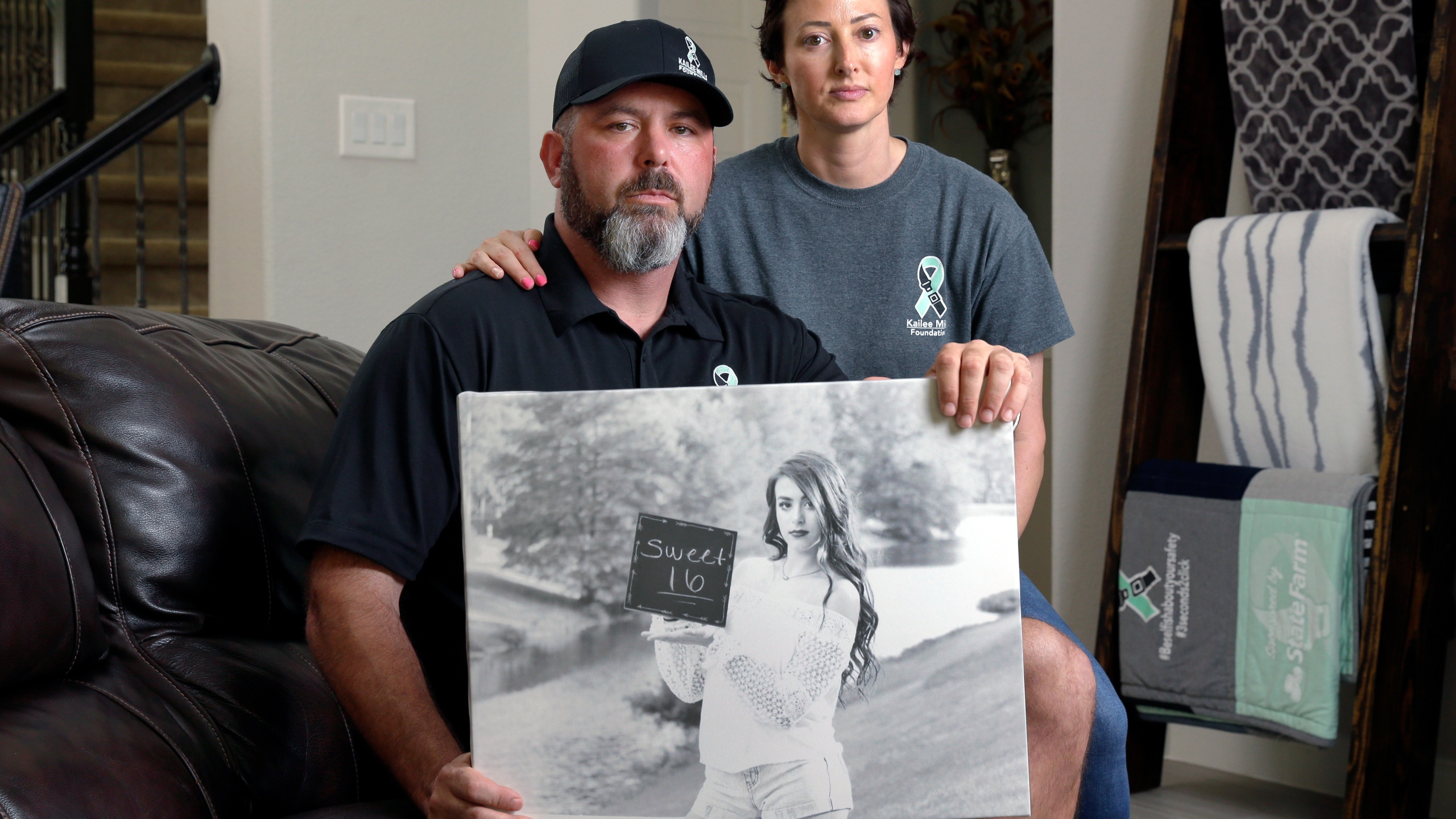 In this Oct. 12, 2021, photo, David and Wendy Mills, parents of Kailee Mills who was killed four years ago in an automobile accident when riding in the back seat without a seat belt, with a photo of their daughter at their home in Spring, Texas. (AP Photo/Michael Wyke)