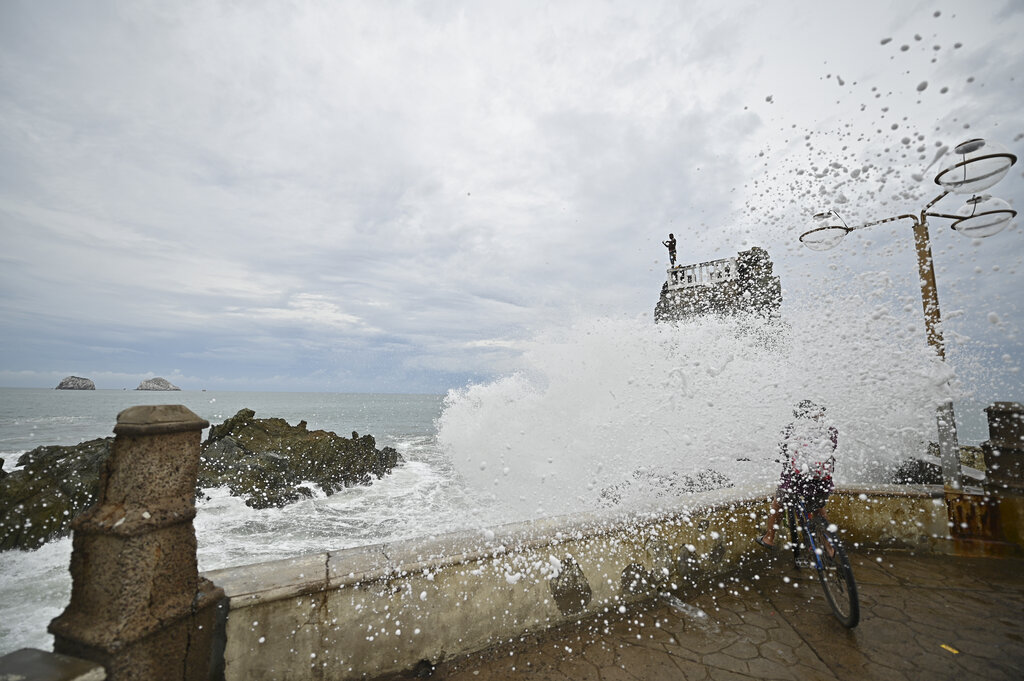 A cyclist is splashed by a crashing wave prior the landfall of tropical storm Pamela, on the boardwalk in Mazatlan, Mexico, Tuesday, Oct. 12, 2021. (AP Photo/Roberto Echeagaray)
