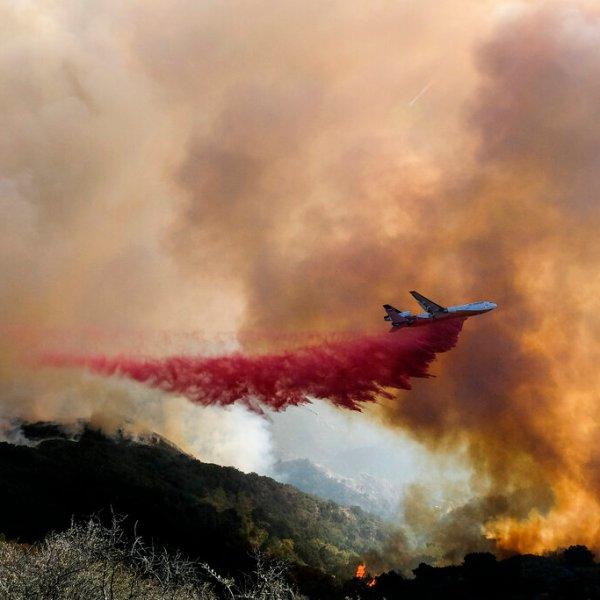 An air tanker drops retardant on a wildfire Wednesday, Oct. 13, 2021, in Goleta, Calif. (AP Photo/Ringo H.W. Chiu)