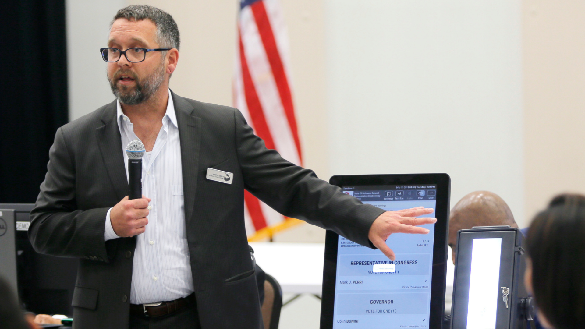 In this Aug. 30, 2018 file photo, Eric Coomer from Dominion Voting demonstrates his company's touch screen tablet that includes a paper audit trail at the second meeting of Secretary of State Brian Kemp's Secure, Accessible & Fair Elections Commission in Grovetown, Ga. Attorneys for President Donald Trump's re-election campaign, its onetime attorney Rudy Giuliani and conservative media figures asked a judge Wednesday, Oct. 13, 2021, to dismiss a defamation lawsuit by Coomer, a former employee of Dominion Voting Systems, who argues he lost his job after being named in false charges as trying to rig the 2020 election. (Bob Andres/Atlanta Journal-Constitution via AP, File)