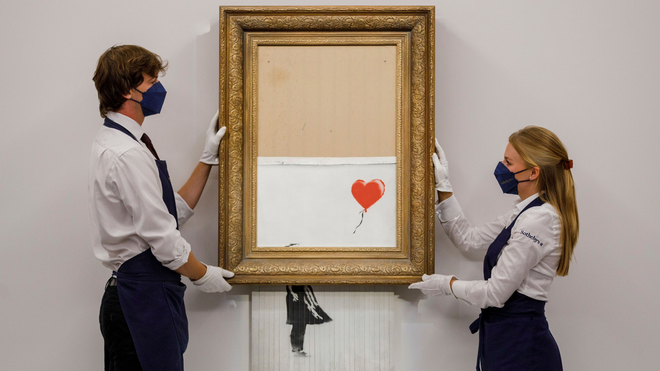 """In this handout photo provided by Sotheby's Auction House, the auction for Banksy's """"Love is the Bin"""" takes place in London, Thursday, Oct. 14, 2021. A work by British street artist Banksy that sensationally self-shredded just after it sold for $1.4 million has sold again for $25.4 million at an auction on Thursday. """"Love is in the Bin"""" was offered by Sotheby's in London, with a presale estimate of $5.5 million to $8.2 million. (Sotheby's Auction House via AP)"""