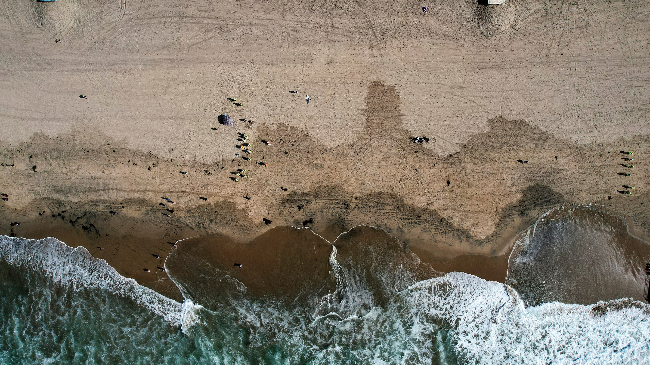 This Monday, Oct. 11, 2021, aerial file photo taken with a drone, shows beachgoers as workers in protective suits continue to clean the contaminated beach in Huntington Beach, Calif. The amount of crude oil spilled in an offshore pipeline leak in Southern California is believed to be close to about 25,000 gallons, a Coast Guard official said Thursday Oct. 14, 2021. (AP Photo/Ringo H.W. Chiu, File)