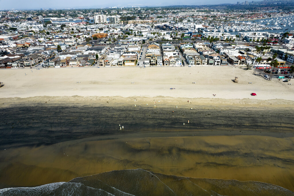 In this Wednesday, Oct.6, 2021 aerial image taken with a drone, workers in protective suits clean the contaminated beach after an oil spill in Newport Beach, Calif. (AP Photo/Ringo H.W. Chiu, File)