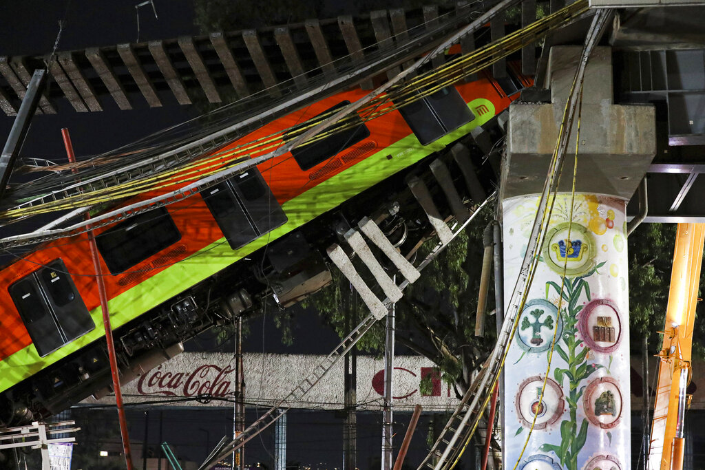 In this May 4, 2021 file photo, Mexico City's subway cars lay at an angle after a section of Line 12 of the subway collapsed in Mexico City. Mexico City´s prosecutor´s office concluded Thursday, Oct. 14, 2021, that the accident was due to mistakes made during the construction of the metro line and that it will prosecute those involved in the crash. (AP Photo/Marco Ugarte, File)