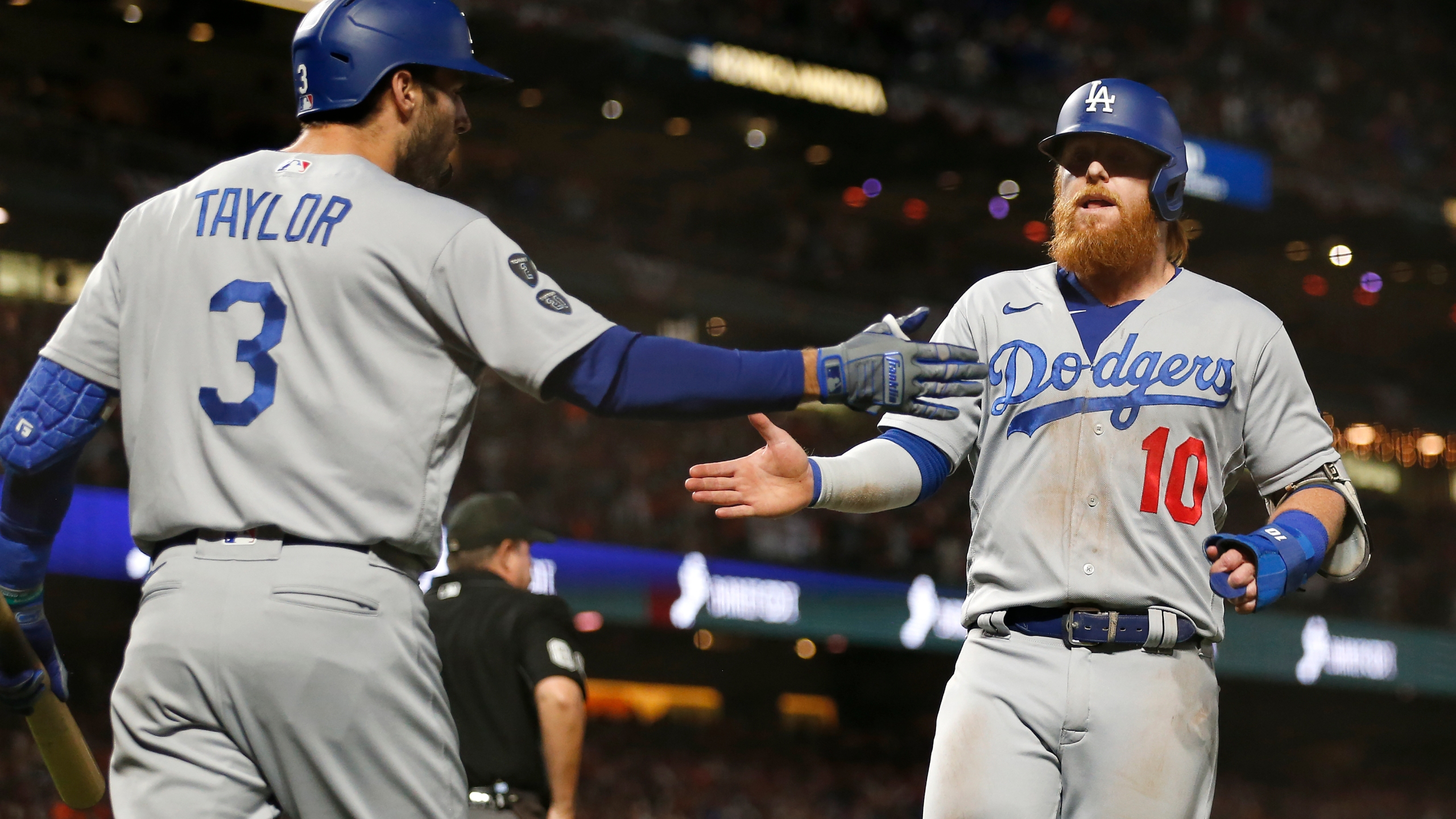 Los Angeles Dodgers' Justin Turner, right, is congratulated by Chris Taylor after scoring against the San Francisco Giants during the ninth inning of Game 5 of a baseball National League Division Series Thursday, Oct. 14, 2021, in San Francisco. (AP Photo/Jed Jacobsohn)