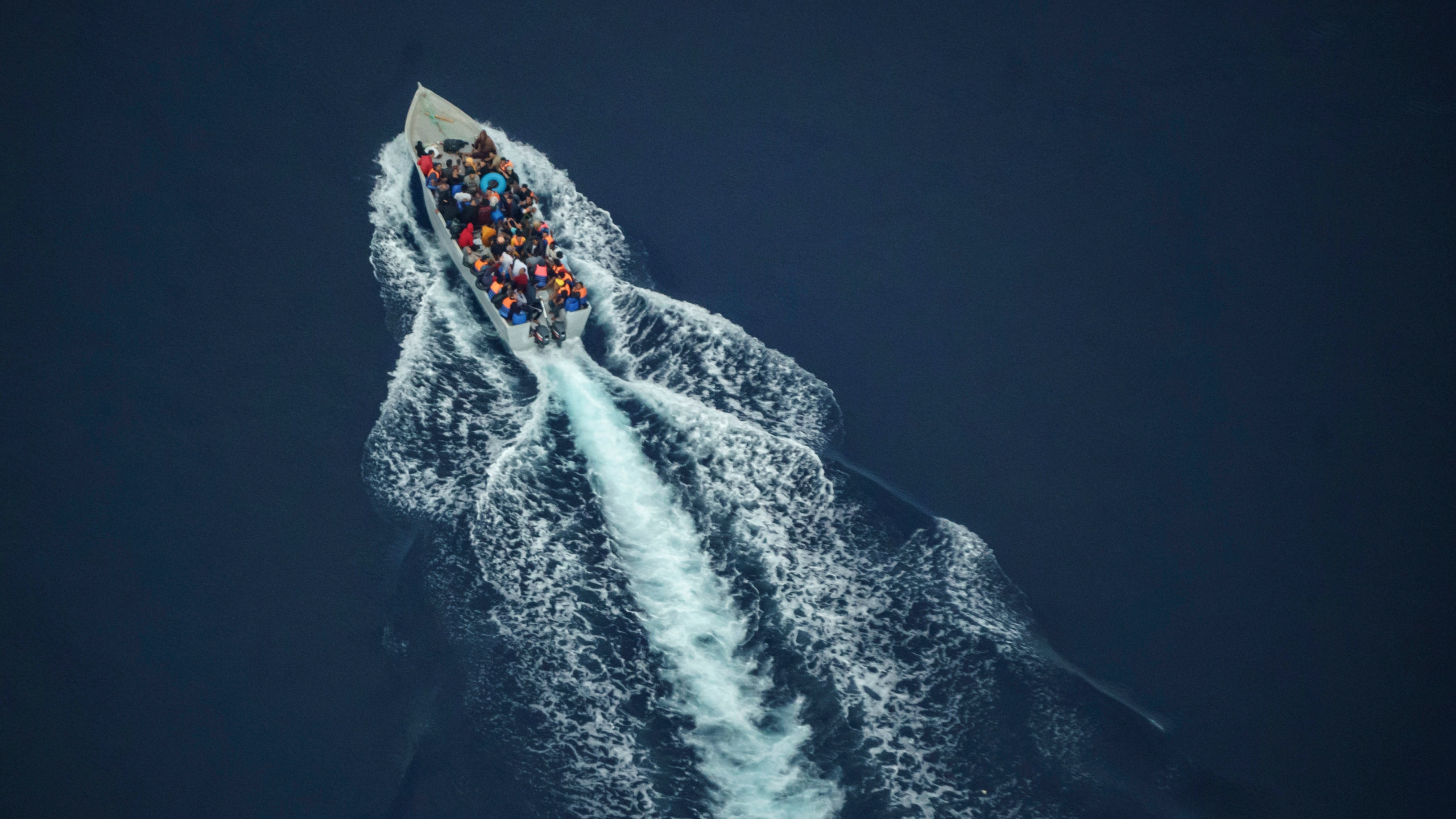 Migrants navigate on an overcrowded wooden boat in the Central Mediterranean Sea between North Africa and the Italian island of Lampedusa, Saturday, Oct. 2, 2021, as seen from aboard the humanitarian aircraft Seabird. At least 23,000 people have died or disappeared trying to reach Europe since 2014, according to the United Nations' migration agency. Despite the risks, many migrants say they'd rather die trying to reach Europe than be returned to Libya. (AP Photo/Renata Brito)