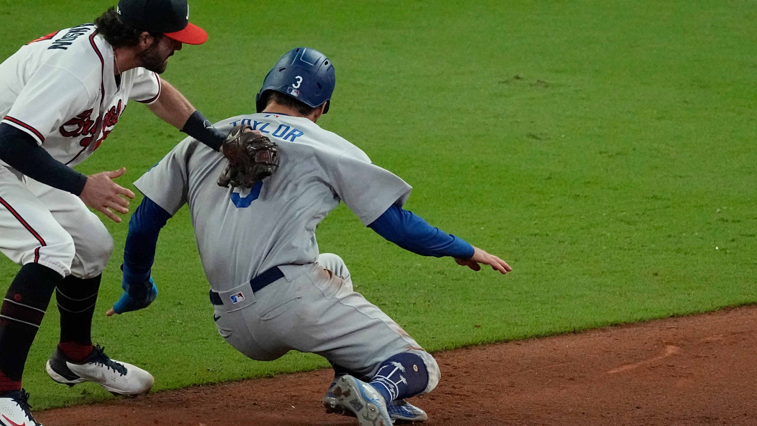 Los Angeles Dodgers' Chris Taylor (3) is tagged out by Atlanta Braves shortstop Dansby Swanson after being caught in a run down on base hit by Dodgers' Cody Bellinger during the ninth inning in Game 1 of baseball's National League Championship Series Saturday, Oct. 16, 2021, in Atlanta. (AP Photo/John Bazemore)