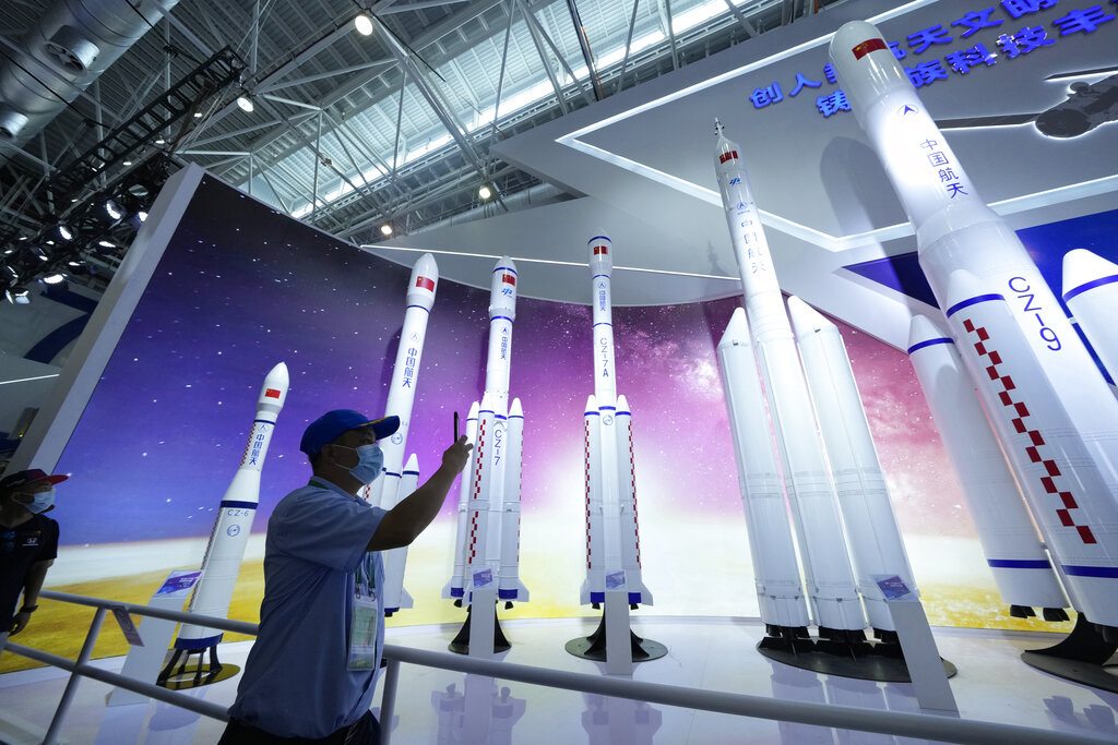 In this Sept. 29, 2021, file photo, a visitor takes photos of replicas of space launch rockets Airshow China 2021 in Zhuhai, southern China's Guangdong province. (AP Photo/Ng Han Guan, File)