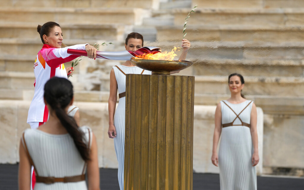 Greece's Olympic Cross Country Ski Champion Paraskevi Ladopoulou, left, lights the flame during the Olympic flame handover ceremony at Panathinean stadium in Athens, Greece, Tuesday, Oct. 19, 2021. (AP Photo/Thanassis Stavrakis)