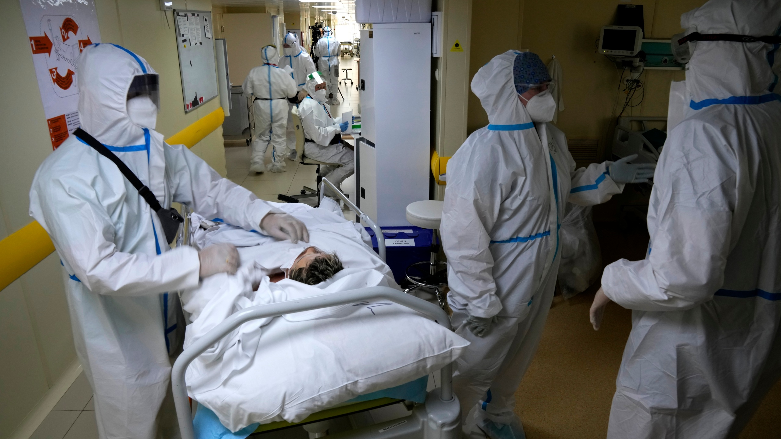 Medics wearing special suits to protect against coronavirus prepare to move a patient with coronavirus at an ICU at the Moscow City Clinical Hospital 52, in Moscow, Russia on Oct. 19, 2021. (AP Photo/Alexander Zemlianichenko)
