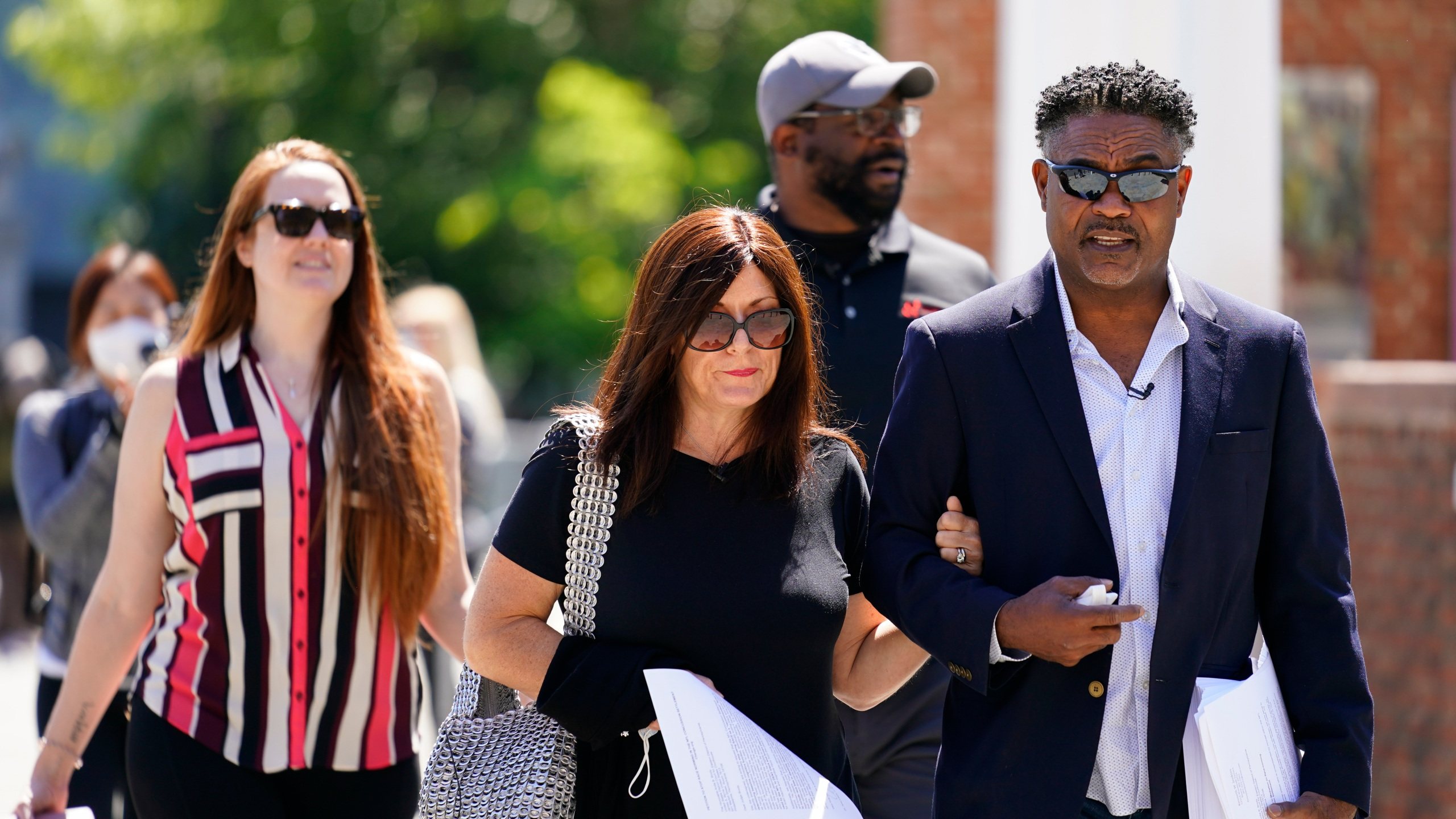 In this May 14, 2021, file photo, former NFL players Ken Jenkins, right, and Clarence Vaughn III, center right, along with their wives, Amy Lewis, center, and Brooke Vaughn, left, carry petitions demanding equal treatment for everyone involved in the settlement of concussion claims against the NFL, to the federal courthouse in Philadelphia on May 14, 2021. (Matt Rourke/Associated Press)
