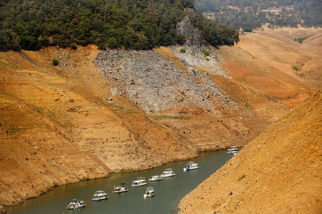 In this Aug. 14, 2021, file photo, houseboats rest in a channel at Lake Oroville State Recreation Area in Butte County, Calif. (AP Photo/Noah Berger, File)
