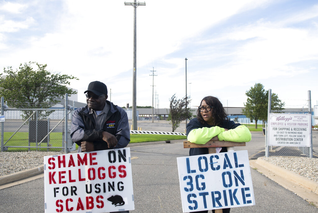 Larry Gamble, who has worked at the Kellogg plant for 13 years, and Sharnita Childress, who has worked at the plant for 8 years, picket with other union workers outside of the plant in Battle Creek, Mich. on Tuesday, Oct. 19, 2021. (Nicole Hester/The Grand Rapids Press via AP)