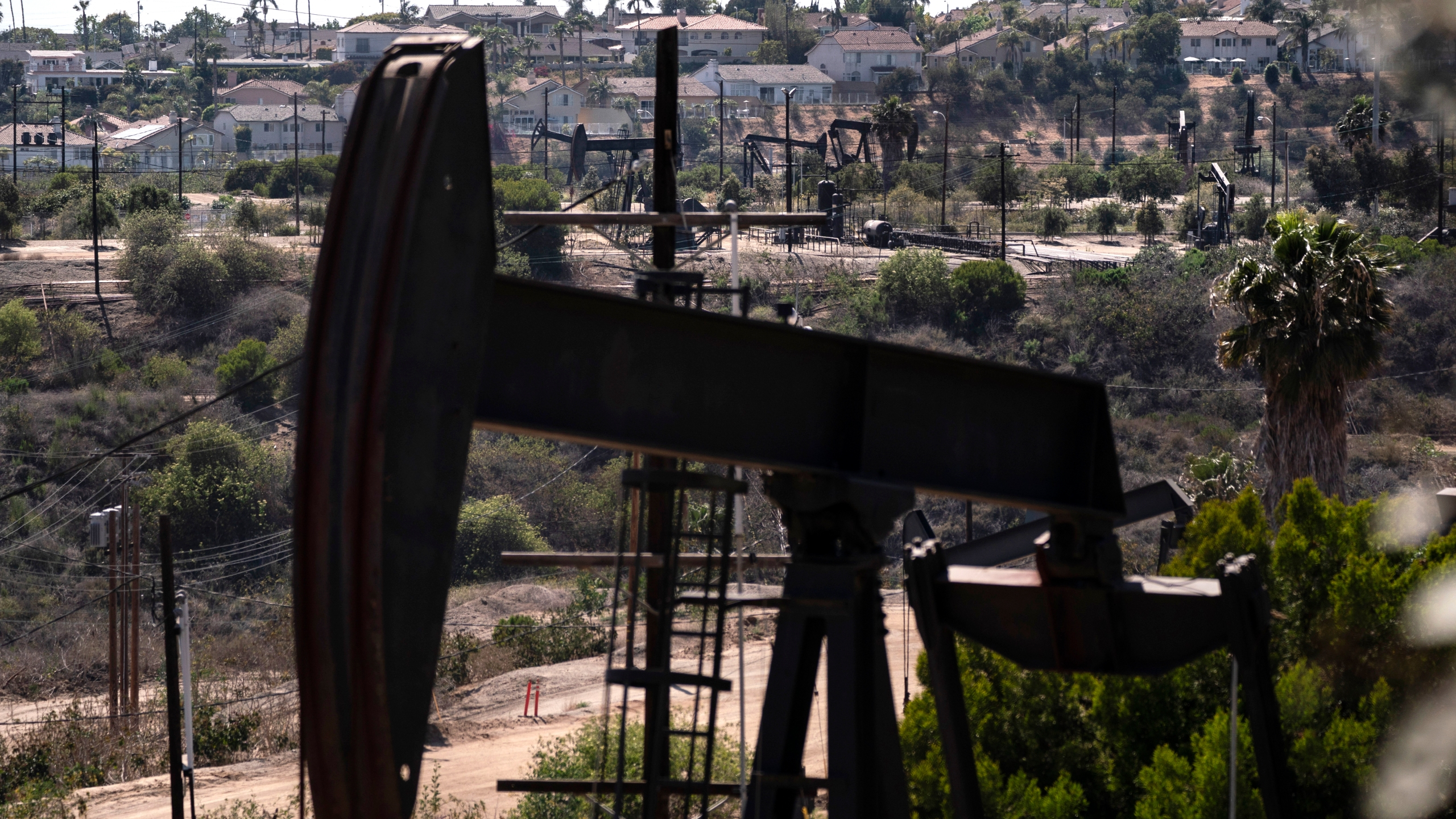 In this May 18, 2021, file photo, homes sit on a hill behind pump jacks operating at the Inglewood Oil Field in Los Angeles. (AP Photo/Jae C. Hong, File)