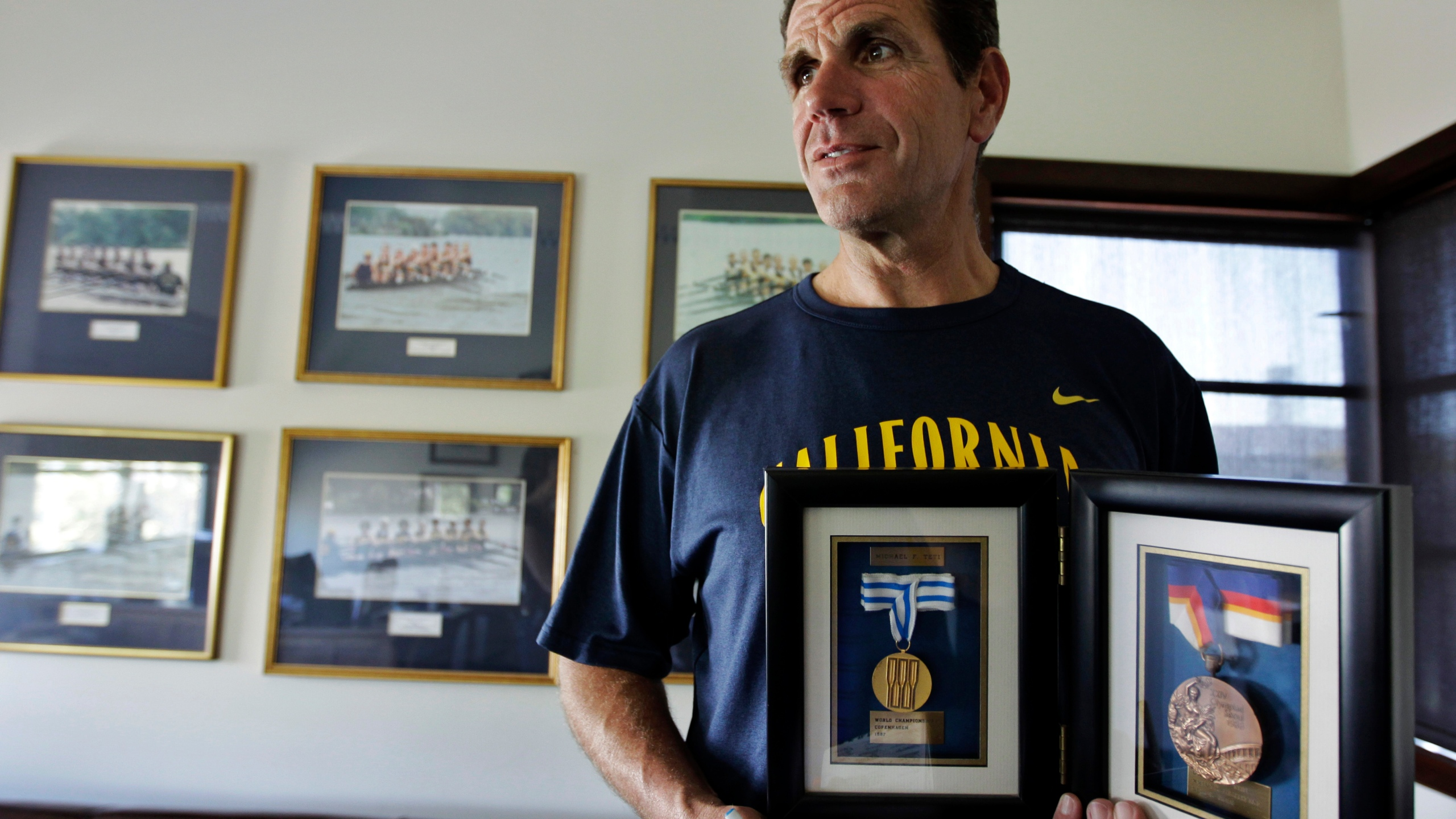 In this May 7, 2012, file photo, coach Mike Teti displays the bronze medal from the Seoul Olympics and the gold medal from the 1987 World Championship in Copenhagen in his office in Oakland, Calif. (AP Photo/Paul Sakuma, File)
