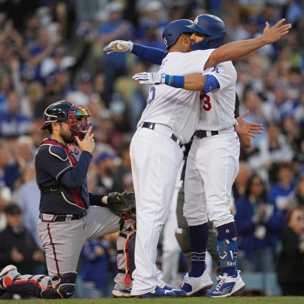 Los Angeles Dodgers' Albert Pujols hugs Chris Taylor after Taylor's two-run home run in the second inning against the Atlanta Braves in Game 5 of baseball's National League Championship Series Thursday, Oct. 21, 2021, in Los Angeles. Pujols scored on the hit. (AP Photo/Ashley Landis)